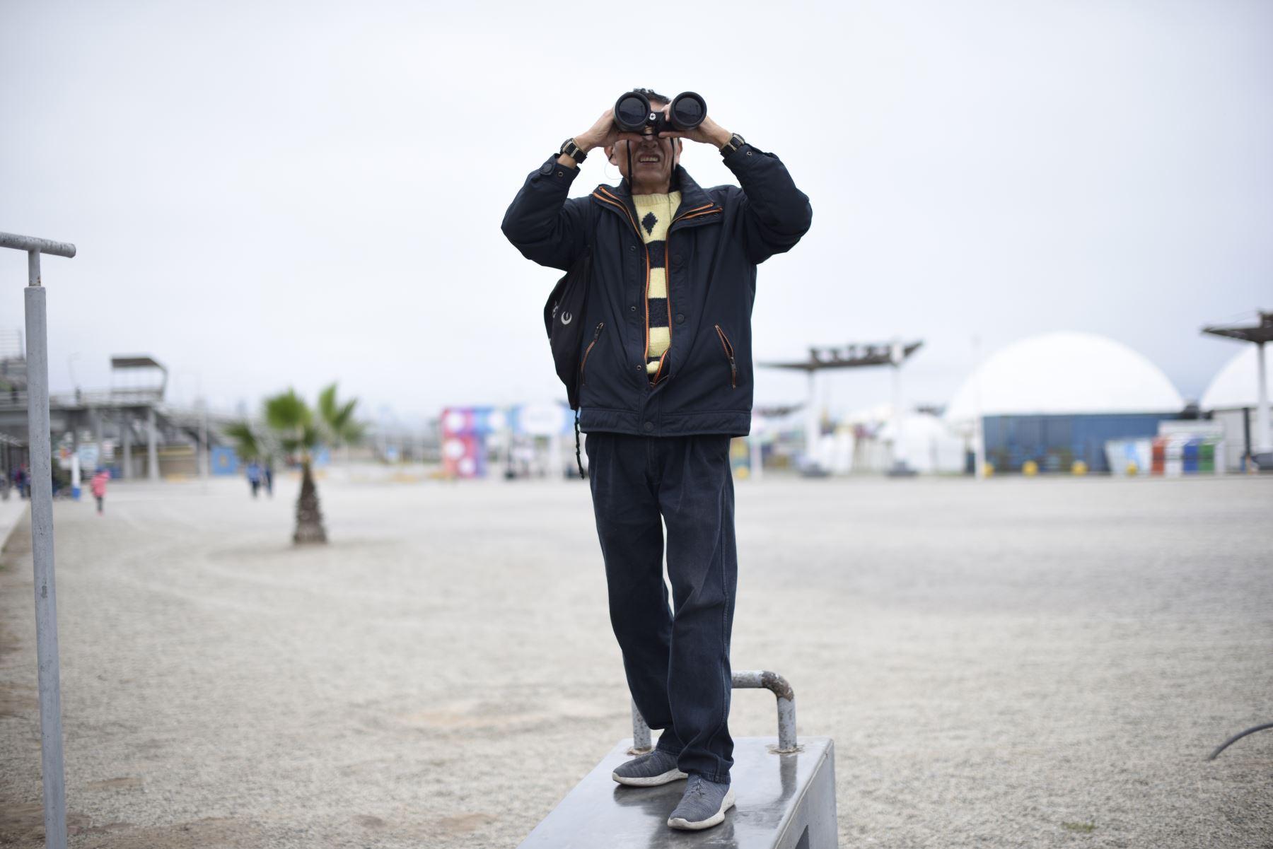 Señor con binoculares observando la competencia de Ciclismo de Ruta en la Costa Verde. Foto: ANDINA/ Lima 2019