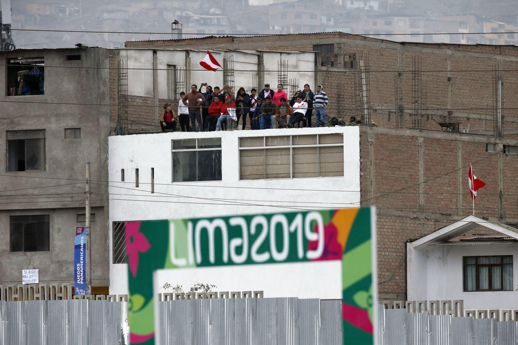 En el techo de una casa de los al rededores del Complejo deportivo Villa Maria del Triunfo, en pleno 28 de Julio, una familia se reúne para presenciar el partido final de Rugby Sevens femenino y masculino. Foto: ANDINA/ Lima 2019
