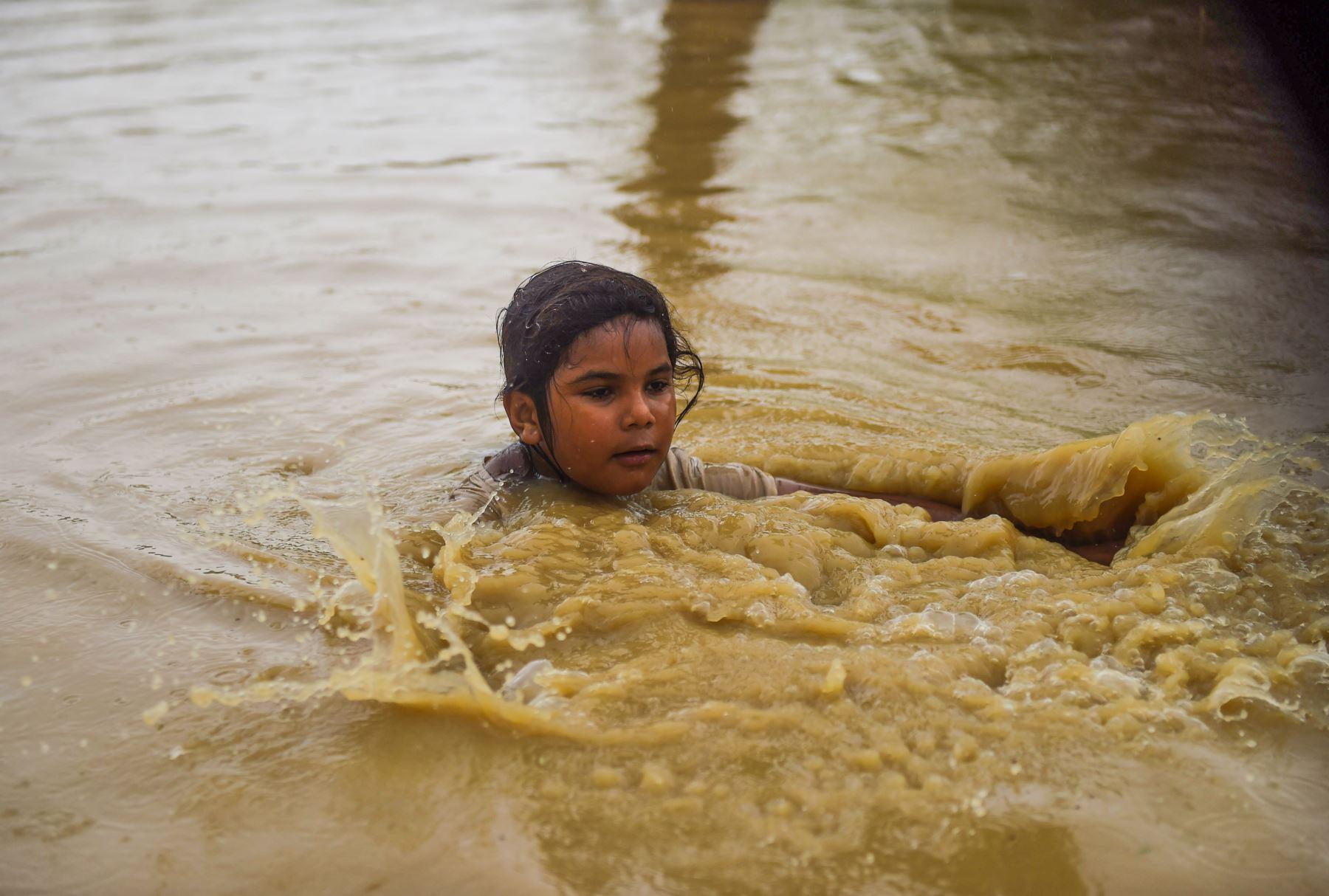 Una niña camina por una calle inundada después de fuertes lluvias monzónicas en las afueras de Karachi. AFP