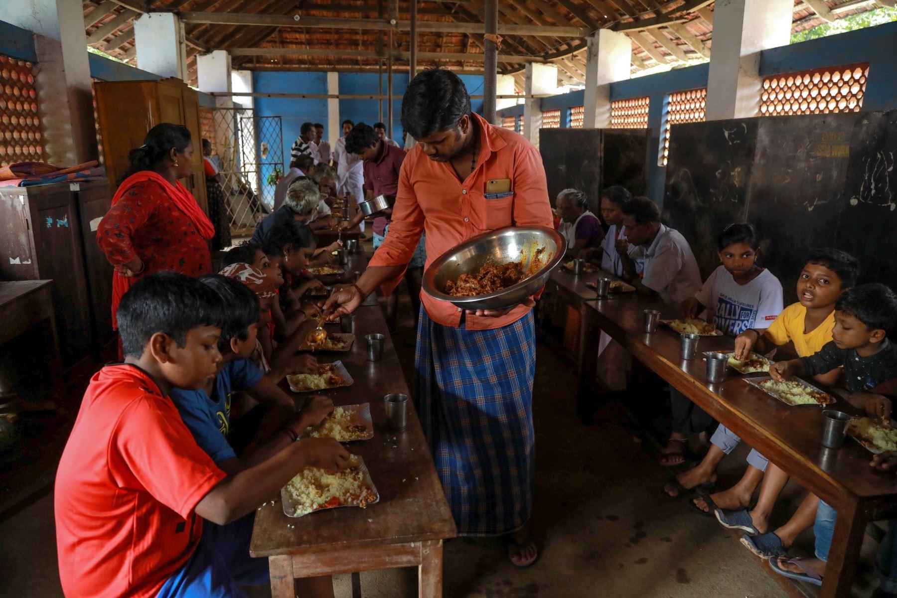 A las personas desplazadas por la inundaciones se les sirve comida en un campamento de ayuda en Kunnukara al sur de India. AFP