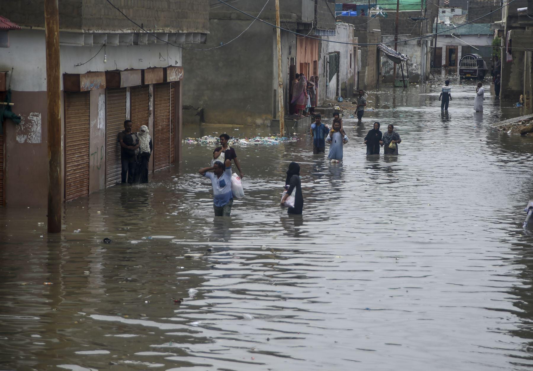 Los residentes caminan por una calle inundada después de fuertes lluvias monzónicas en Karachi. AFP