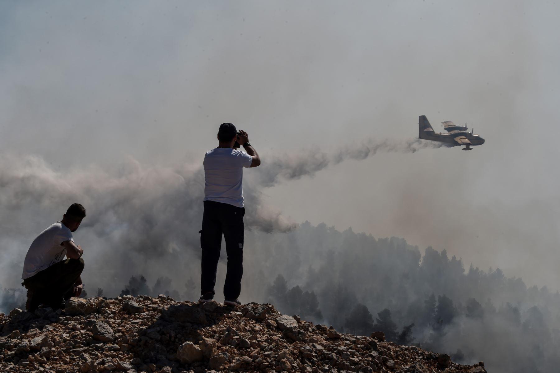 Un avión arroja agua sobre un incendio forestal cerca del pueblo de Stavros, en la isla griega de Evia: Foto: AFP