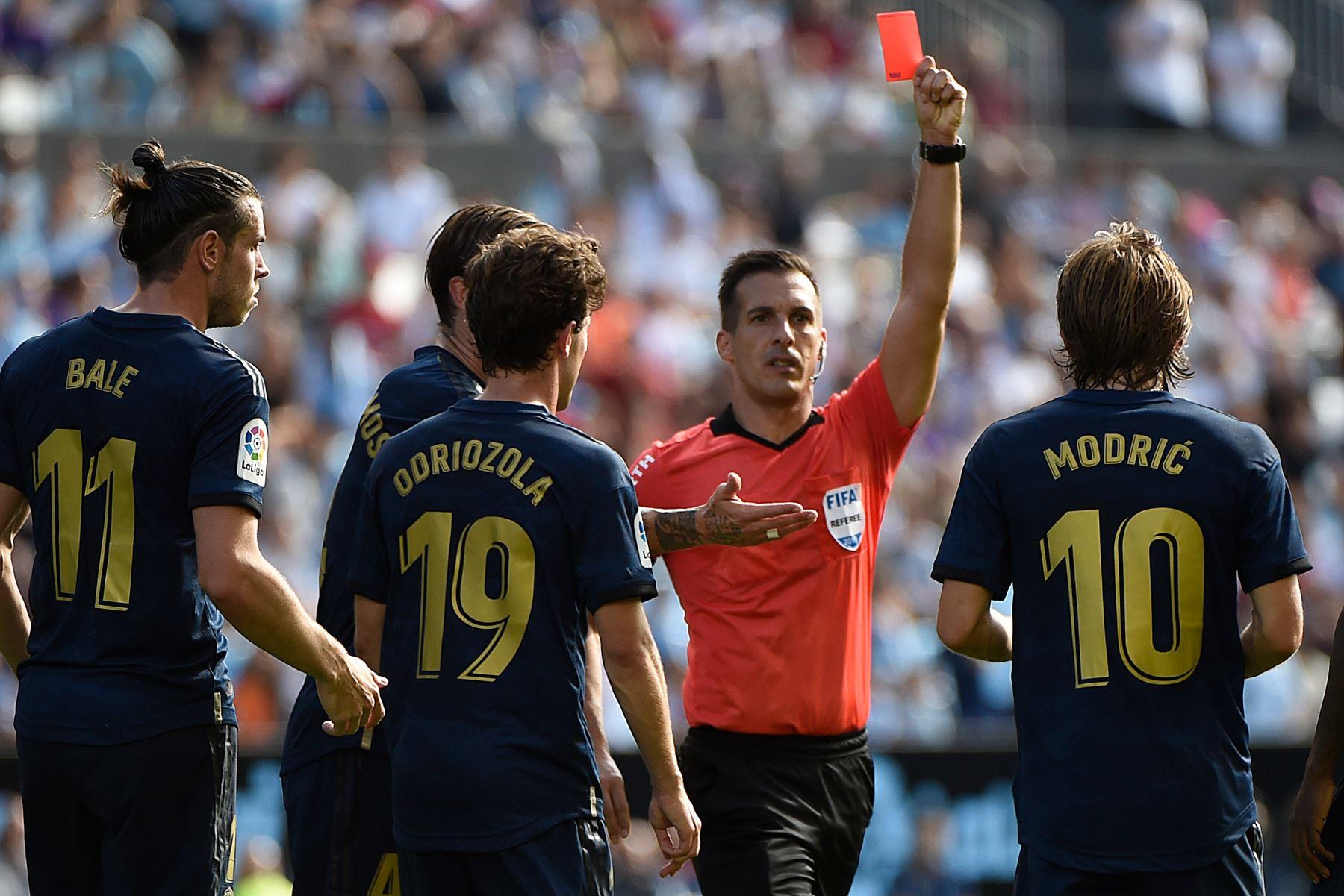El centrocampista croata del Real Madrid Luka Modric (R) recibe una tarjeta roja del árbitro español Xavier Estrada Fernández durante el partido de fútbol de la Liga española entre Celta Vigo y el Real Madrid. Foto: AFP