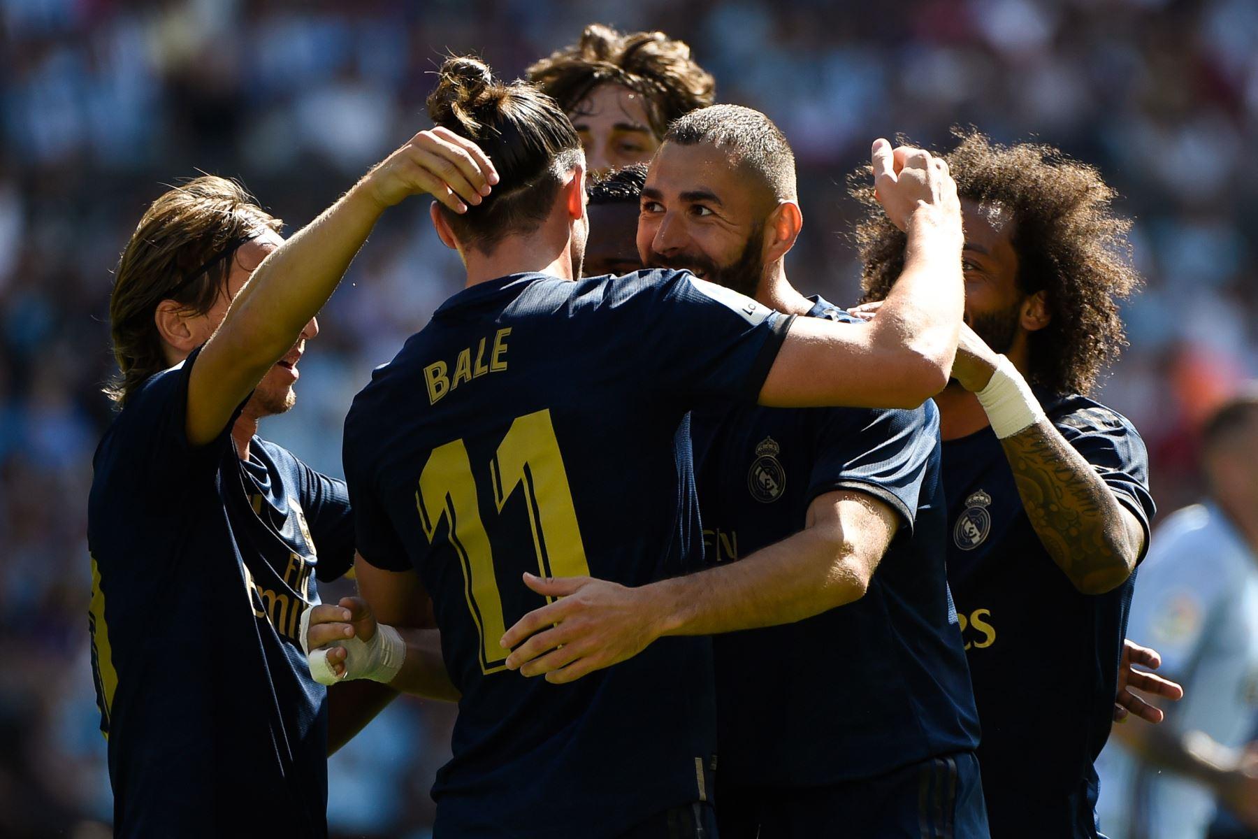 El delantero francés del Real Madrid Karim Benzema (C) celebra con sus compañeros de equipo después de marcar un gol durante el partido de fútbol de la Liga española entre el Celta de Vigo y el Real Madrid. Foto: AFP