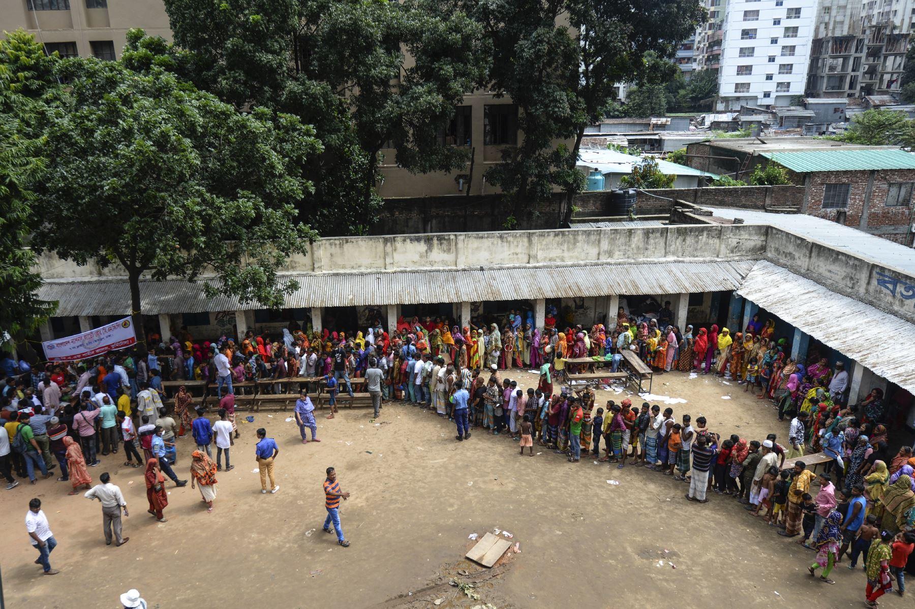 Los residentes de los barrios marginales hacen cola para comer en Dhaka , después de que un incendio estalló en un barrio pobre del barrio de Mirpur. Al menos 10,000 personas están sin hogar después de que un incendio masivo arrasó un barrio pobre lleno de gente en la capital de Bangladesh. Foto: AFP