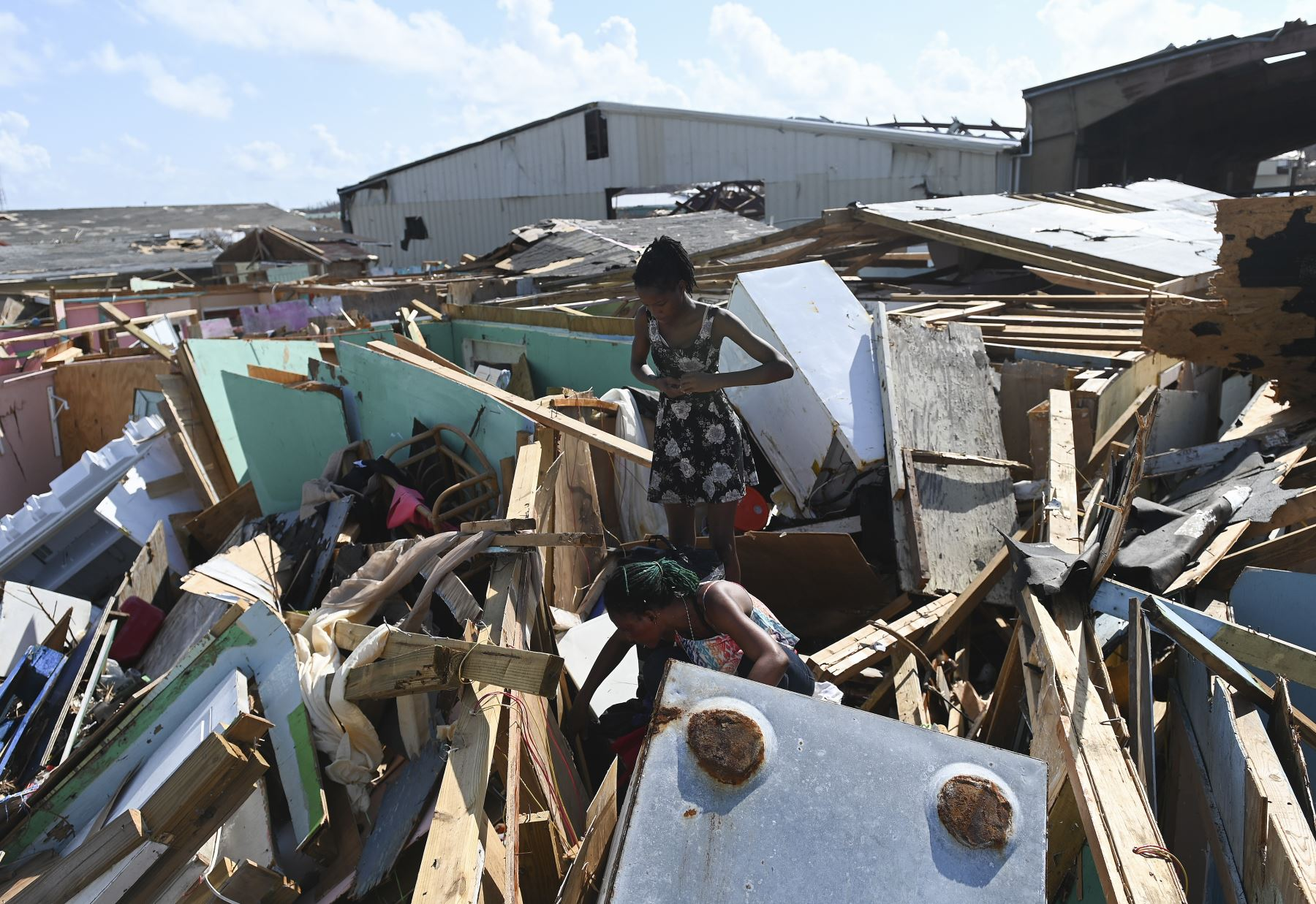 Margie Gerthadauphin (abajo) y su hija Kimberly observan su casa destruida mientras intenta salvar sus pertenencias en Marsh Harbour, Bahamas, una semana después del paso del huracán Dorian. Foto:AFP