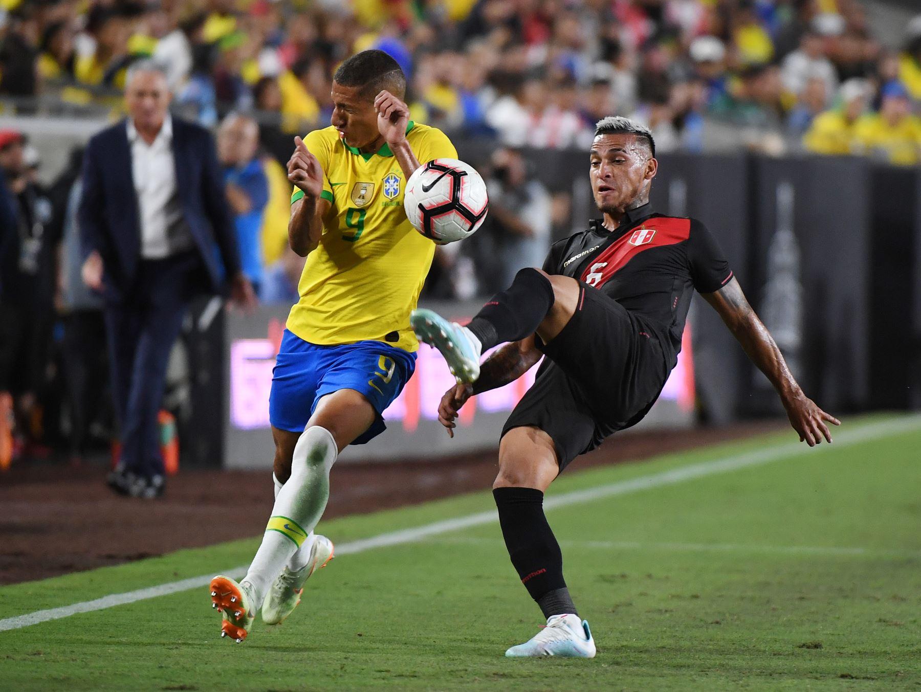 Richarlison de Brasil (L) es abordado por Miguel Trauco de Perú (R) durante el partido amistoso de fútbol internacional entre Brasil y Perú en el Los Angeles Memorial Coliseum, en Los Ángeles, California, el 10 de septiembre de 2019. Foto: AFP
