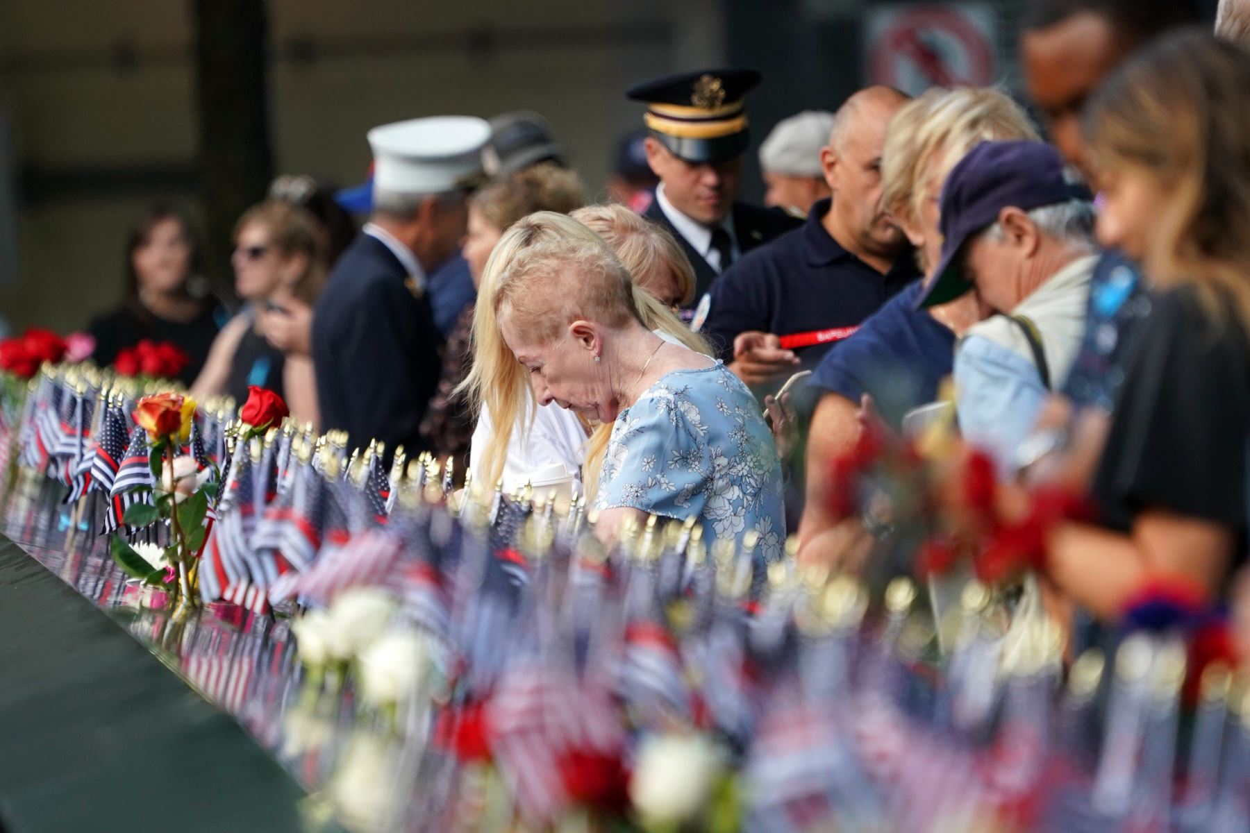 La gente deja flores y banderas durante la Ceremonia de Conmemoración del 11 de septiembre en el 9/11 Memorial en el World Trade Center  en Nueva York. Foto: AFP