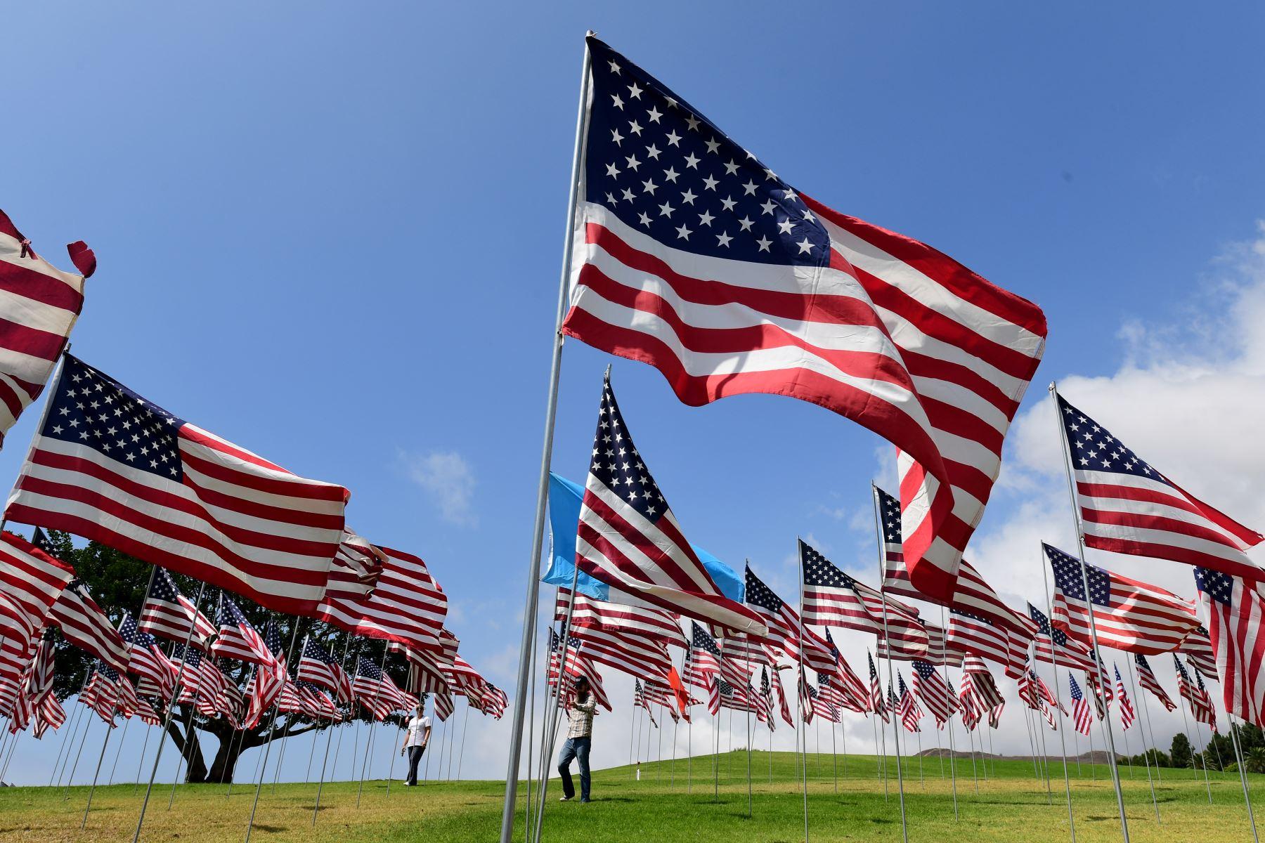 La gente visita la exhibición de la Onda de Banderas de Pepperdine en la Universidad de Pepperdine en Malibú, California, conmemorando a los que murieron en los ataques del 11 de septiembre de 2001 con 2,977 banderas.  Foto :AFP