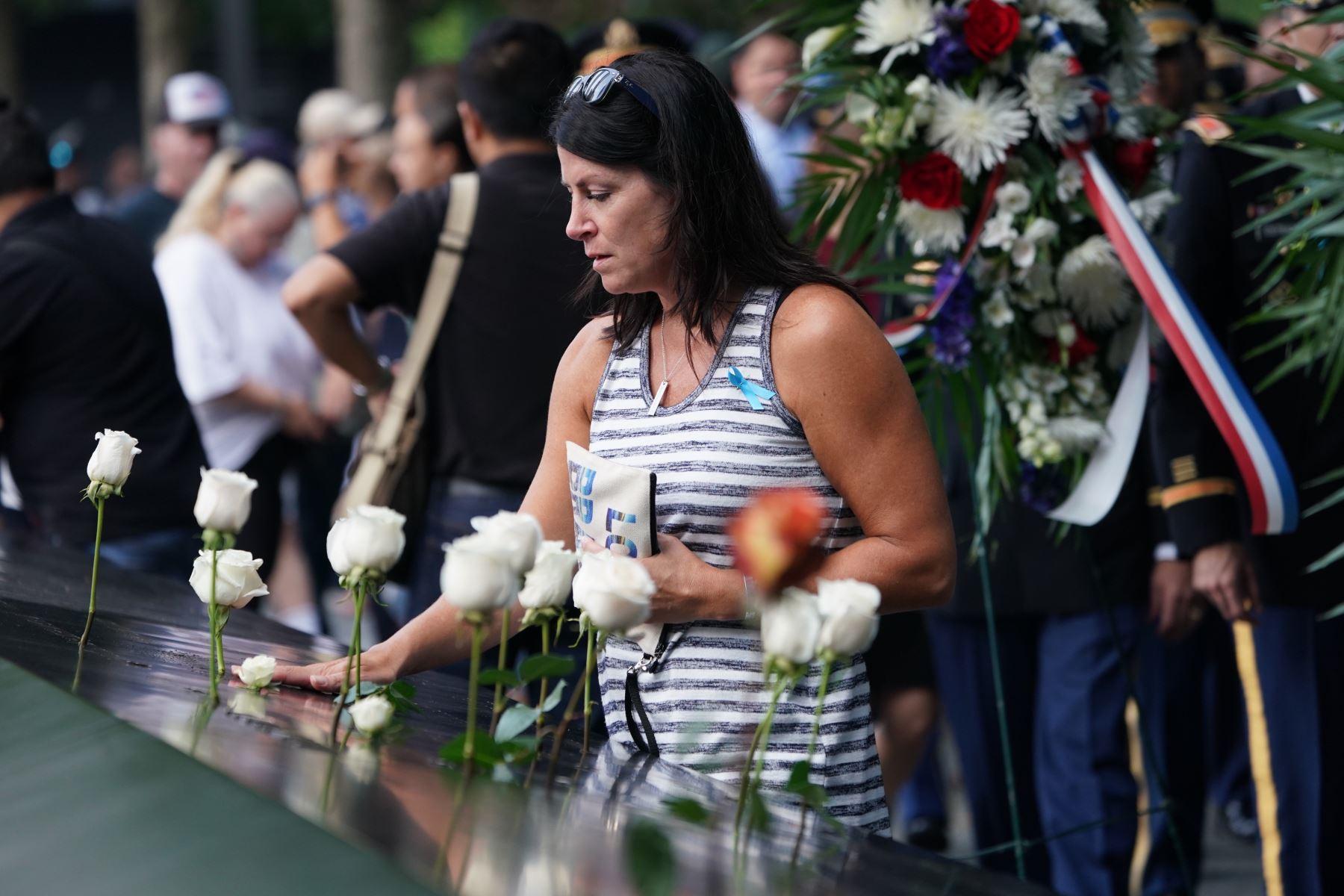 La gente deja flores durante la Ceremonia de Conmemoración del 11 de septiembre en el 9/11 Memorial en el World Trade Center  en Nueva York. Foto :AFP