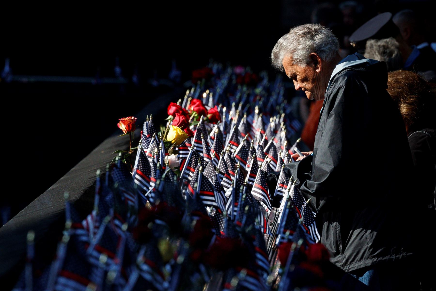 Un hombre acaricia el monumento conmemorativo que rinde homenaje a los bomberos fallecidos durante los atentados del 11 de septiembre de 2001,durante el 18 aniversario de la tragedia, en Nueva York. Foto: AFP