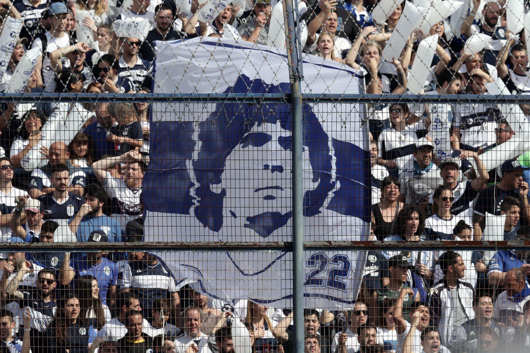 Los partidarios de Gimnasia y Esgrima La Plata animan a su equipo y a su nuevo entrenador, la ex estrella del fútbol argentino Diego Armando Maradona, durante su partido de fútbol de la Superliga de Primera División de Argentina contra el Racing Club. Foto: AFP