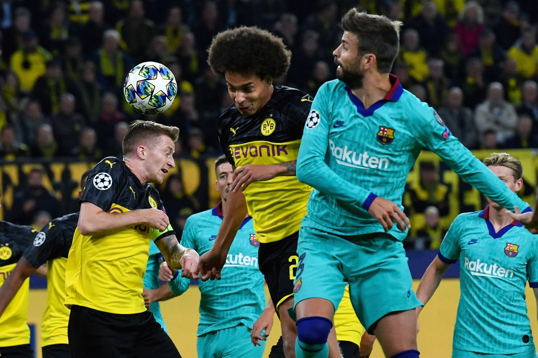 El alero alemán de Dortmund Marco Reus (L) y el mediocampista belga de Axel Witsel compiten por el balón con el defensa del Barcelona Gerard Piqué durante el partido de fútbol del Grupo F de la Liga de Campeones de la UEFA.Foto:AFP
