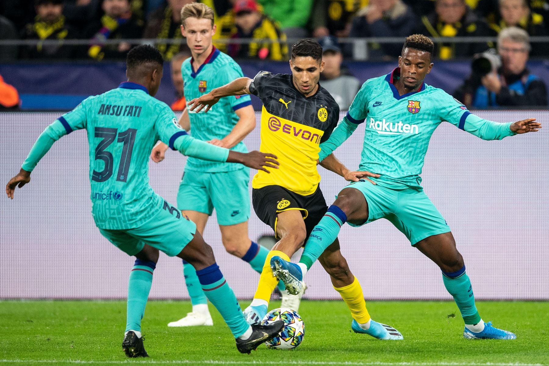 El defensor marroquí de Dortmund Achraf Hakimi (C) compite por el balón con el delantero de Guinea-Bissau de Barcelona Ansu Fati (L) y el defensor del Barsa Nelson Semedo (R) durante el partido de fútbol del Grupo F de la Liga de Campeones de la UEFA.Foto:AFP