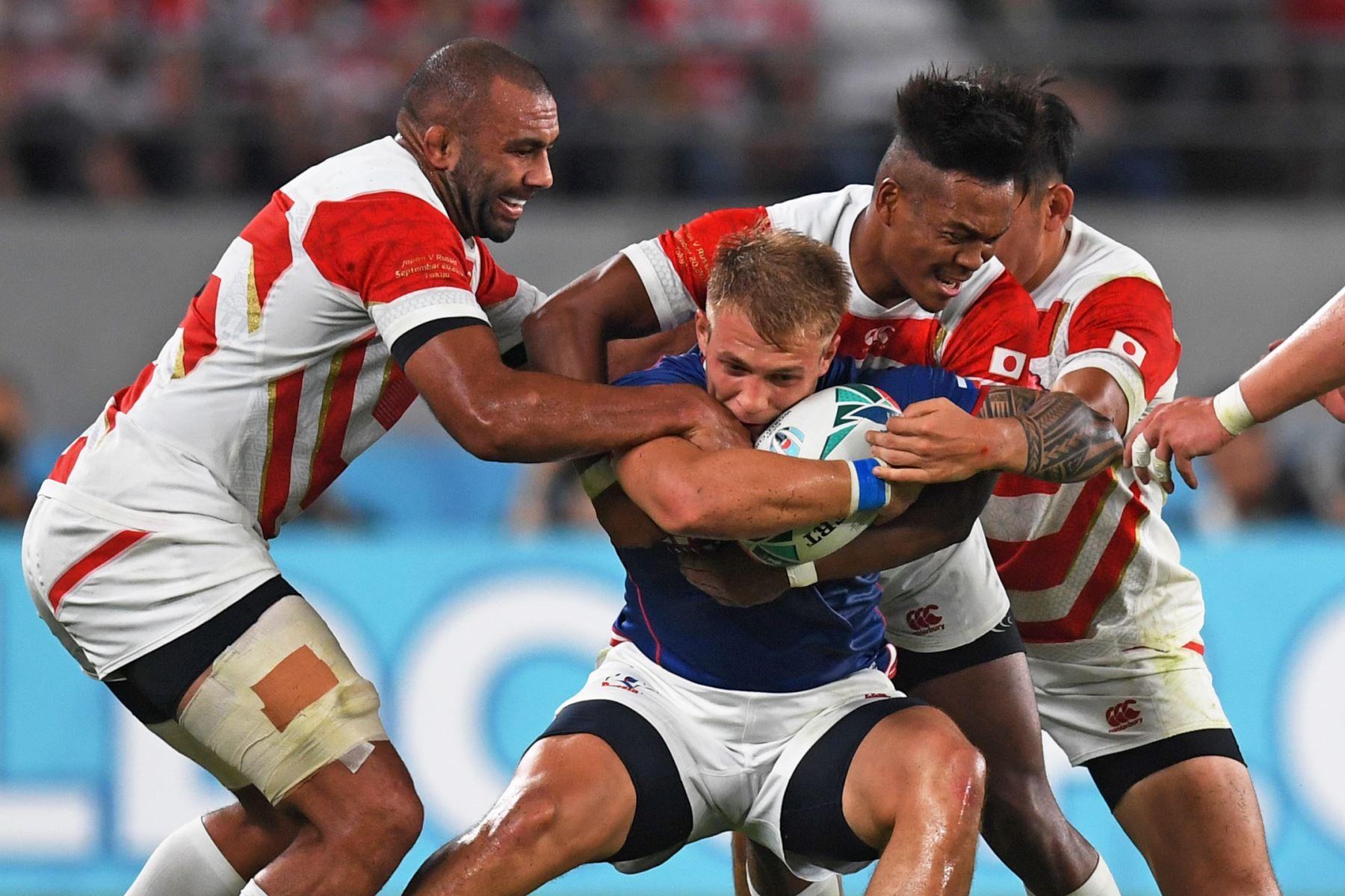 El ala rusa Kirill Golosnitskiy (C) es abordado por los jugadores japoneses durante el partido de la Copa Mundial de Rugby entre Japón y Rusia en Tokio. Foto: AFP