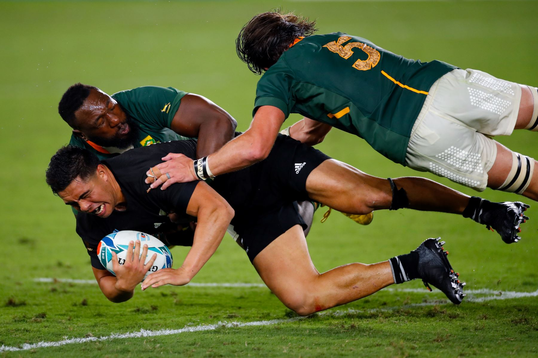 El centro de Nueva Zelanda, Anton Lienert-Brown (L), es abordado por el tenista sudafricano Tendai Mtawarira (C) y bloquea a Franco Mostert durante el partido del Grupo B de la Copa Mundial de Rugby de Japón 2019. Foto: AFP