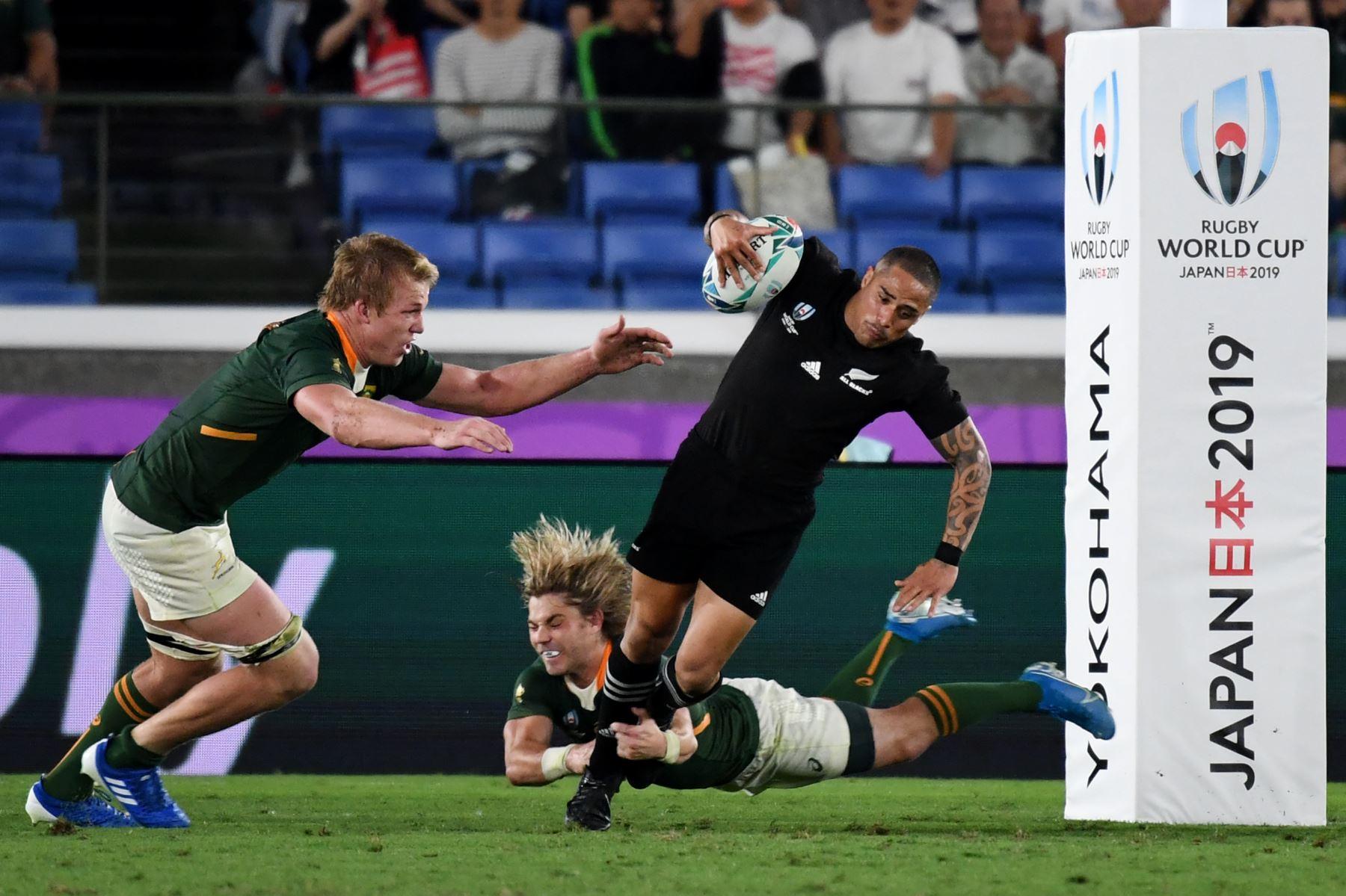 El medio scrum de Sudáfrica Faf de Klerk (abajo) aborda al medio scrum de Nueva Zelanda Aaron Smith (R) junto al compañero de equipo Pieter-Steph Du Toit (L) durante el partido del Grupo B de la Copa Mundial de Rugby de Japón 2019. Foto: AFP