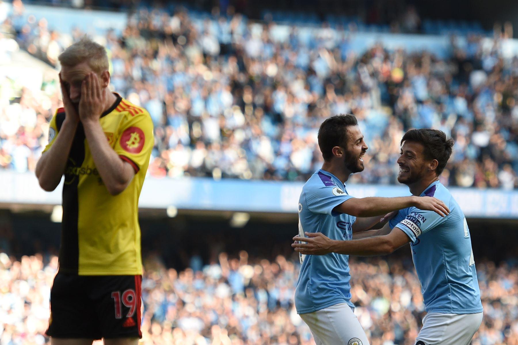 El centrocampista inglés de Watford Will Hughes reacciona cuando el centrocampista portugués del Manchester City Bernardo Silva (CL) celebra con el centrocampista español del Manchester City David Silva. Foto: AFP