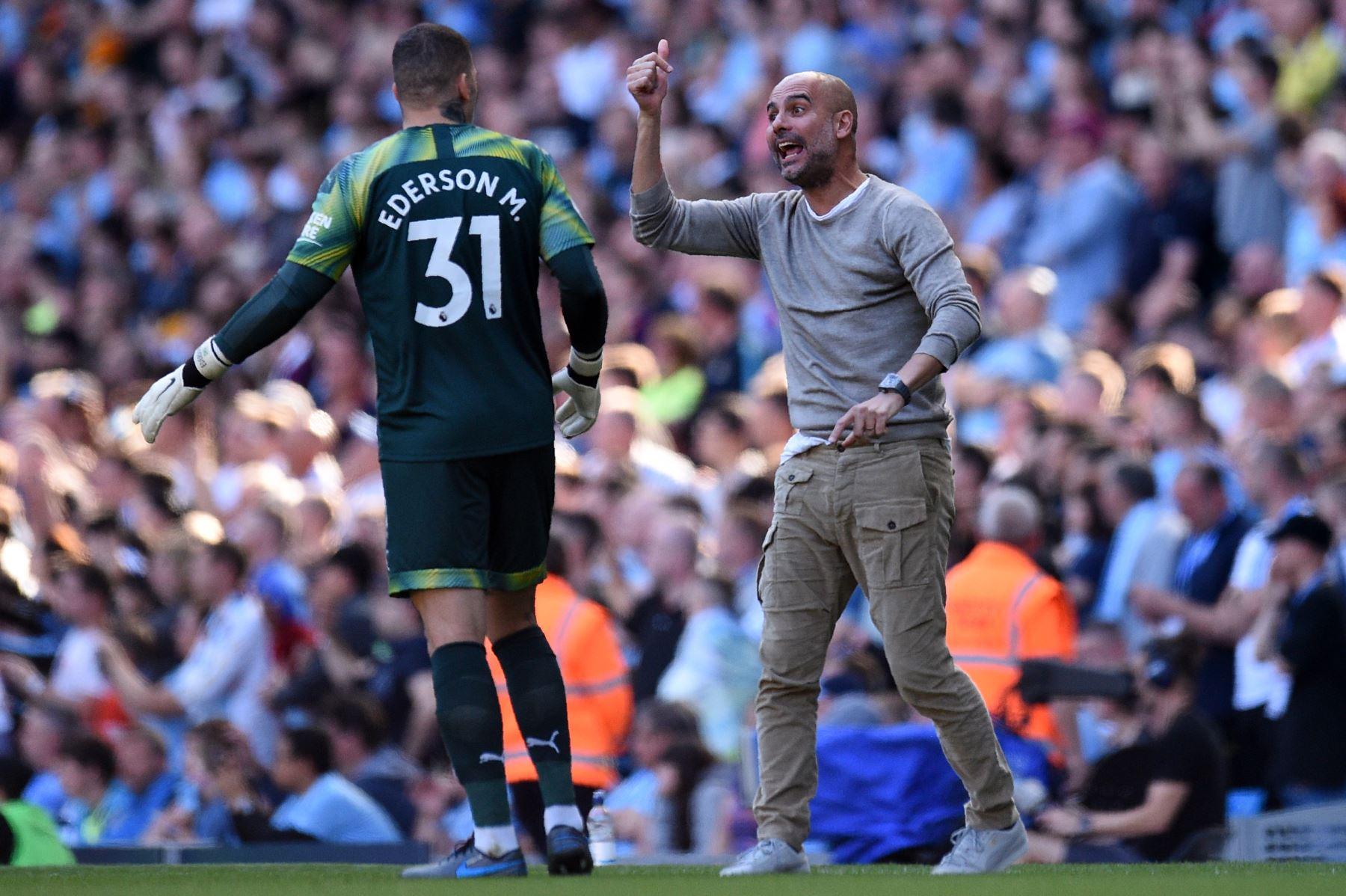 El manager español del Manchester City, Pep Guardiola (R), le hace un gesto al arquero brasileño del Manchester City, Ederson, durante el partido de fútbol de la Premier League inglesa. Foto: AFP