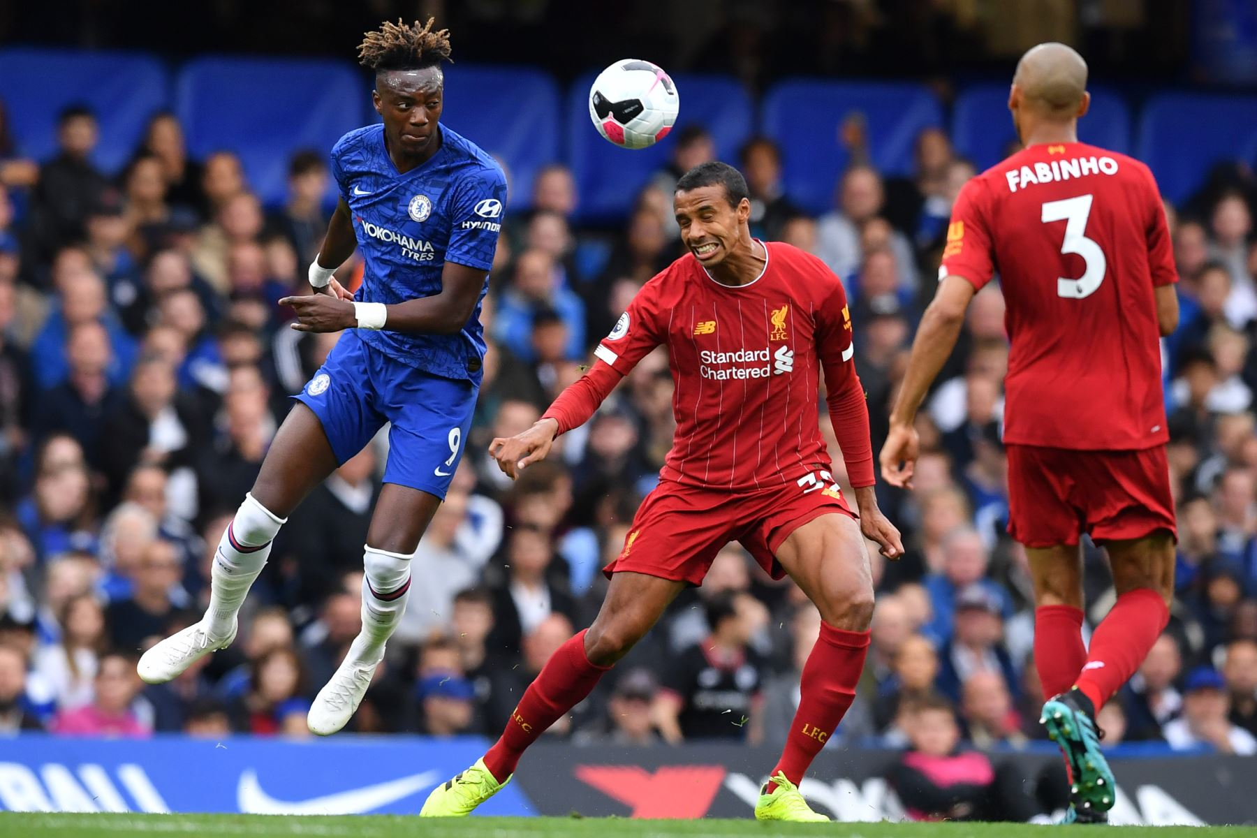 El delantero inglés del Chelsea, Tammy Abraham (L) compite con el defensor camerunés nacido en Alemania Joel Matip (C) durante el partido de fútbol de la Premier League inglesa entre Chelsea y Liverpool. Foto: AFP