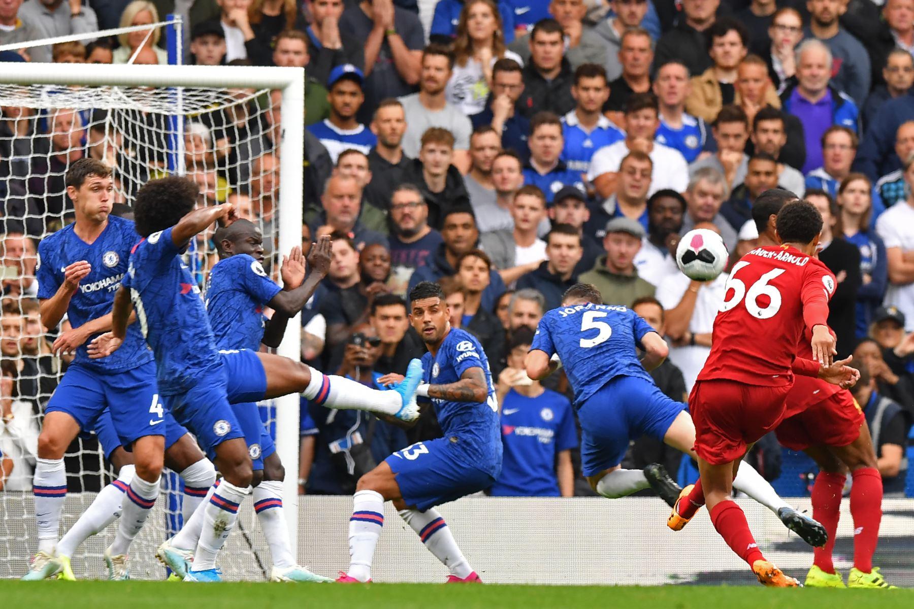El defensor inglés de Liverpool Trent Alexander-Arnold (R) dispara para marcar el gol de apertura durante el partido de fútbol de la Premier League inglesa entre Chelsea y Liverpool. Foto: AFP
