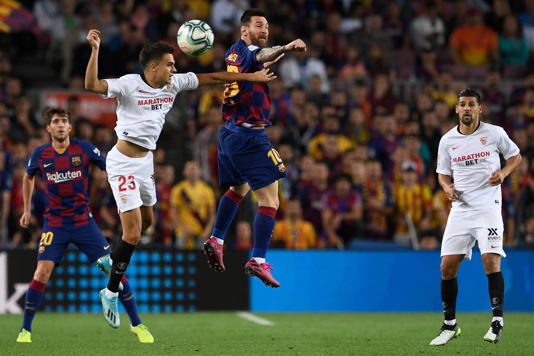 El defensa español de Sevilla Sergio Reguilon compite un balón aéreo contra el astro argentino de Barcelona Lionel Messi. Foto: AFP