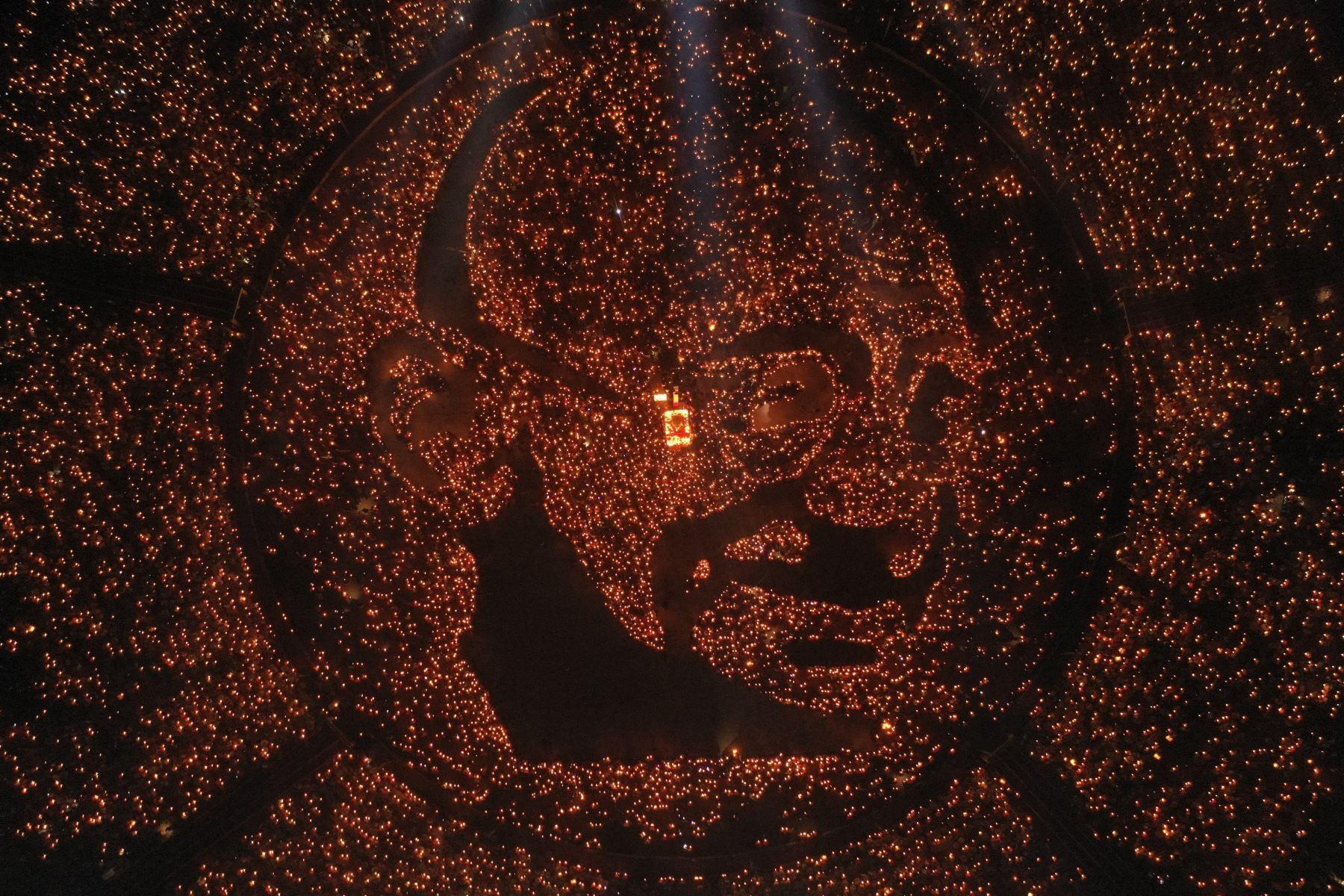 Retrato del ícono de la independencia india Mahatma Gandhi iluminado por 30,000 miles de devotos hindúes sosteniendo lámparas de aceite encendidas para conmemorar su 150 aniversario de nacimiento mientras participan en un Maha Aarti (un ritual hindú), en la India occidental.