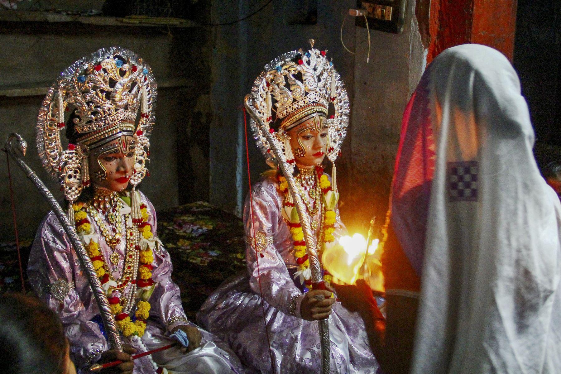 Artistas vestidos como el dios hindú Rama (L) y su compañero Laxman se sientan dentro de un templo antes de una procesión religiosa en la India. Foto: AFP