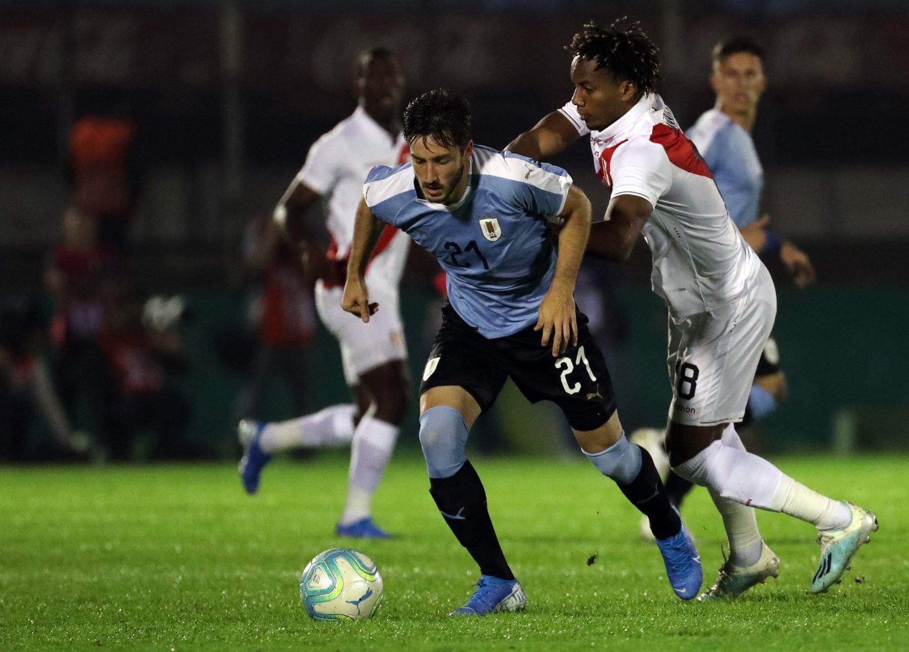 Matías Viña de Uruguay disputa el balón con André Carrillo de Perú en el estadio Centenario de Uruguay, en Montevideo. Foto: EFE