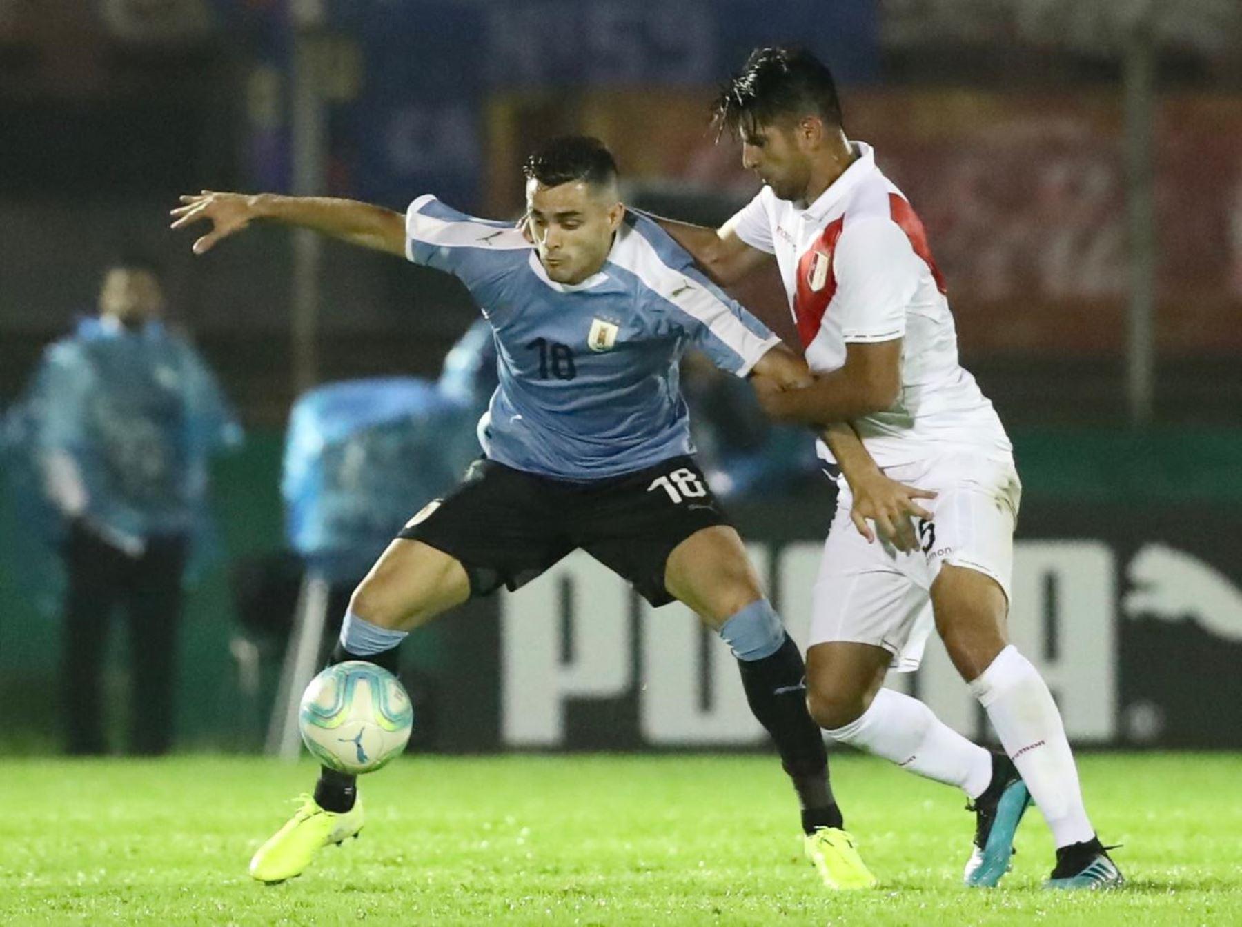 Maxi Gomez de Uruguay intenta proteger el balón ante marca del defensor peruano Carlos Zambrano. Foto: FPF