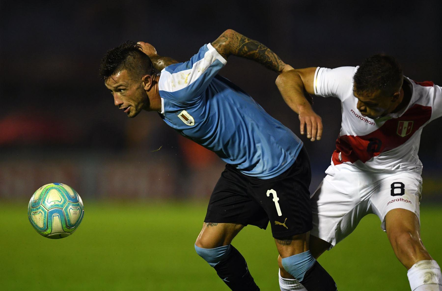 El centrocampista uruguayo Brian Lozano compite por el balón con el delantero peruano Gabriel Costa. Foto: AFP
