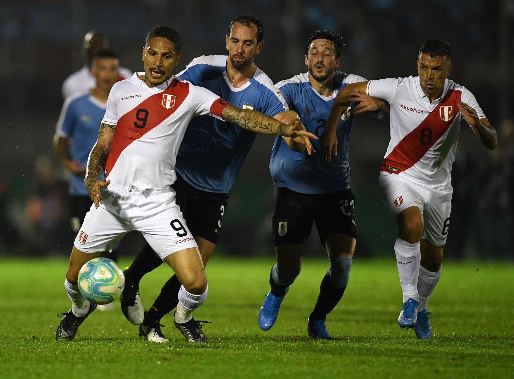 El delantero peruano Paolo Guerrero controla el balón ante la presión del uruguayo Diego Godin. Foto: AFP