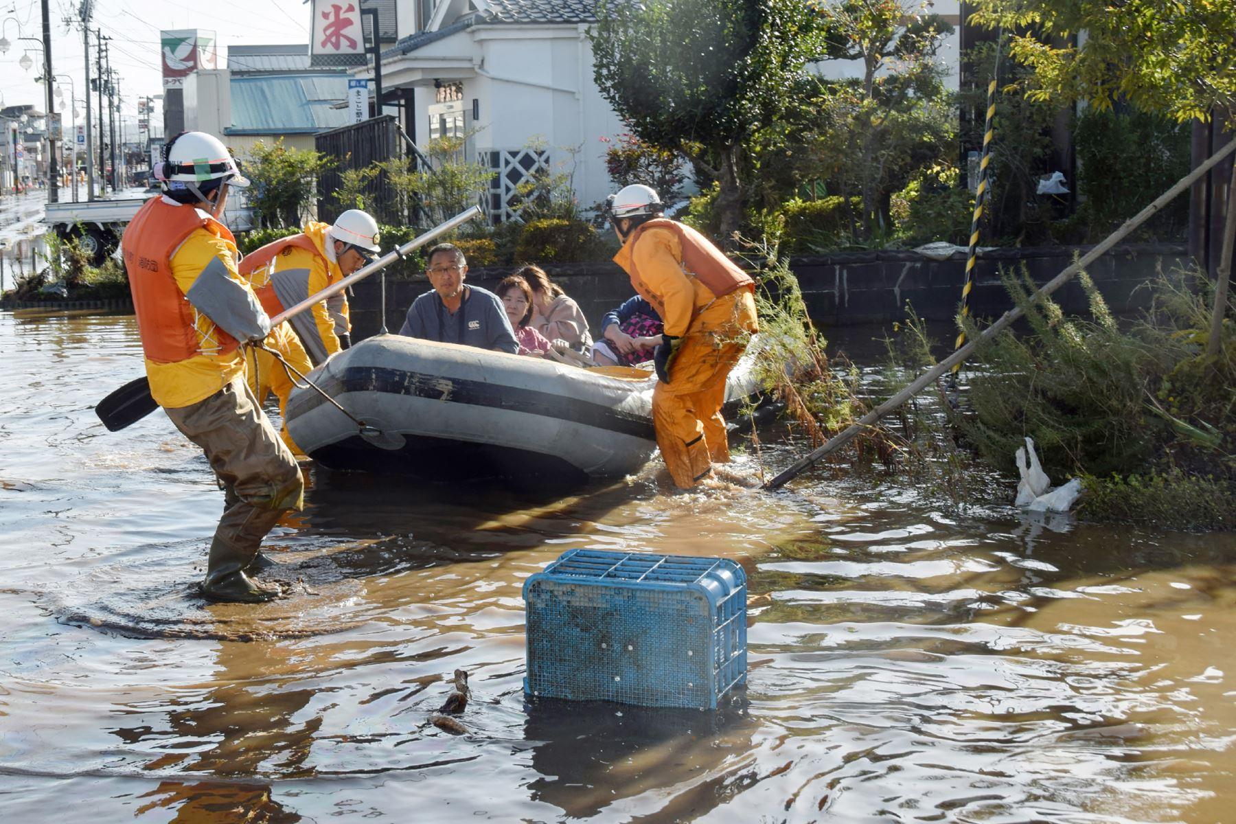 Bomberos evacuan a los residentes de un área inundada en Date, prefectura de Fukushima, un día después de que el tifón Hagibis se extendiera por el centro y el este de Japón. Foto: AFP