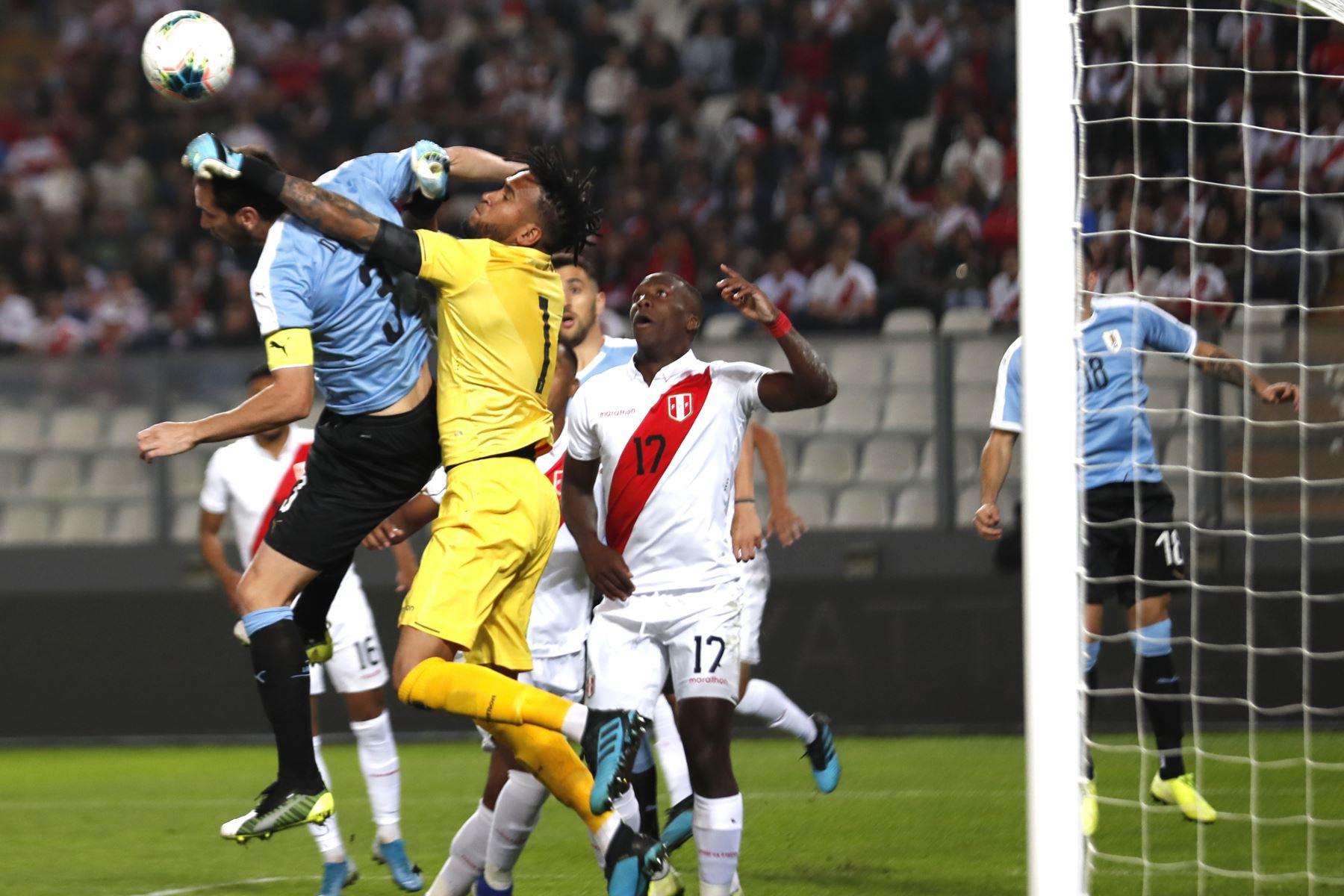 El portero Pedro Gallese de Perú disputa la pelota con Diego Godin de Uruguay durante el partido amistoso en el que Perú gana 1-0, Estadio Nacional de Lima. Foto: ANDINA/ Carlos Lezama