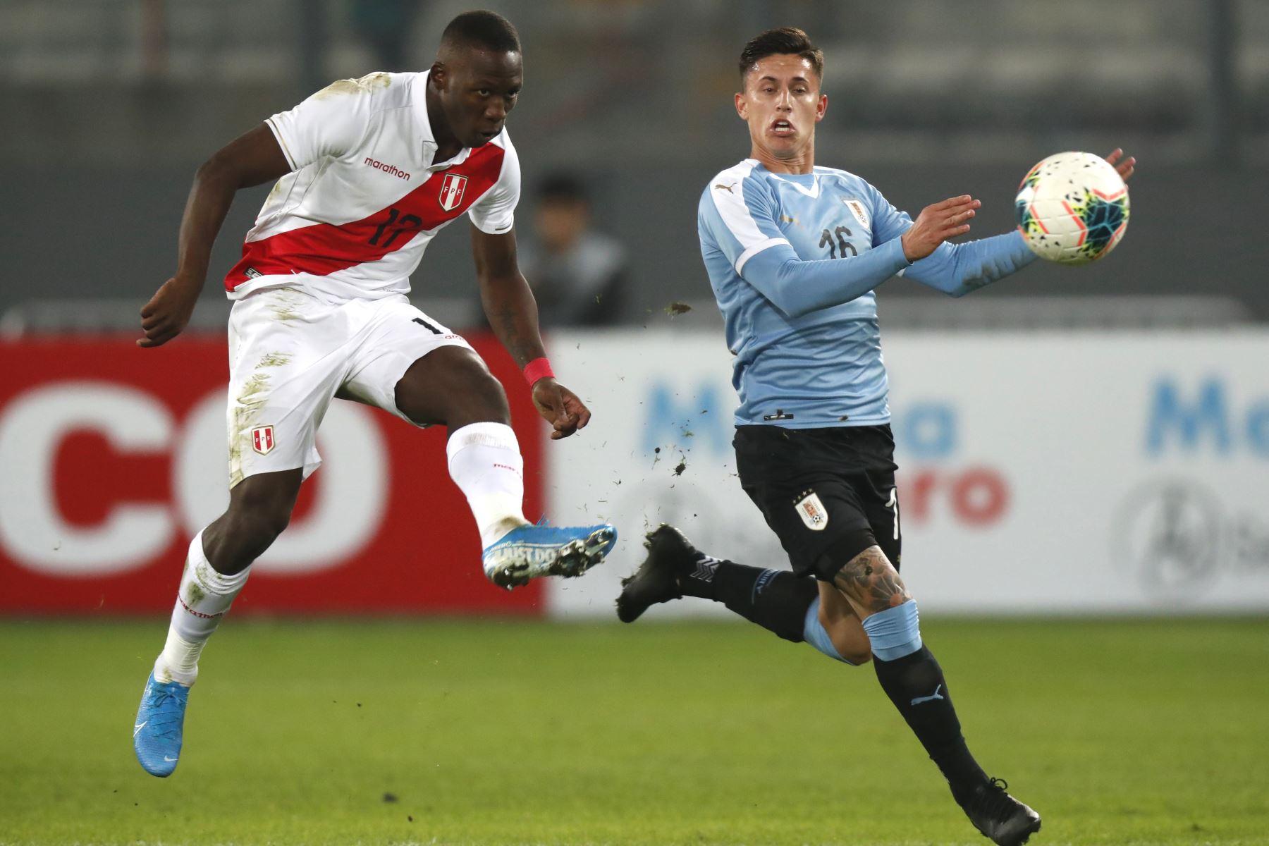 Luis Advíncula de Perú disputa la pelota con Brian Rodríguez de Uruguay durante el partido amistoso en el Estadio Nacional de Lima. Foto: ANDINA/ Carlos Lezama