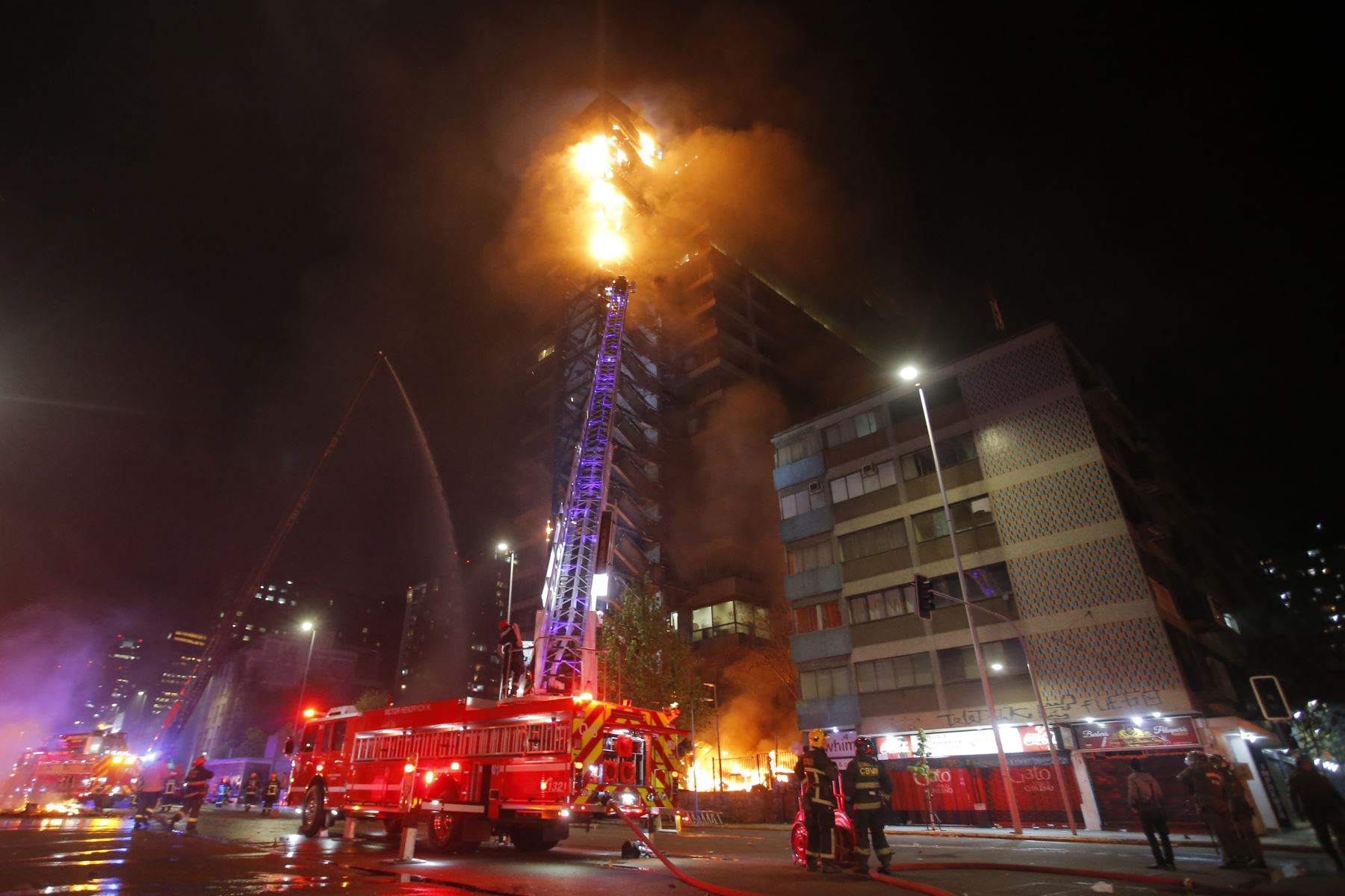 Las llamas envuelven el emblemático edificio en el  centro de Santiago luego de una protesta masiva de evasión de tarifas.  Foto: AFP