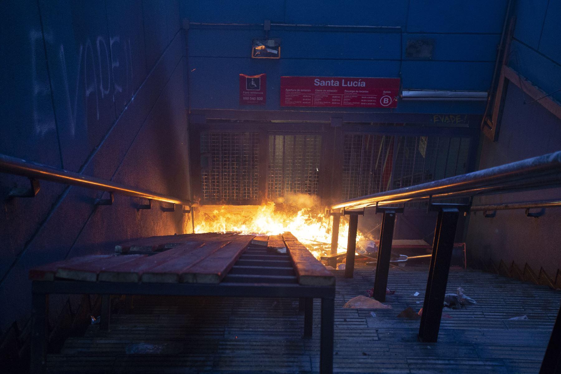 Un incendio provocado por los manifestantes arde en una entrada a la estación de metro de Santa Lucía en Santiago. AFP