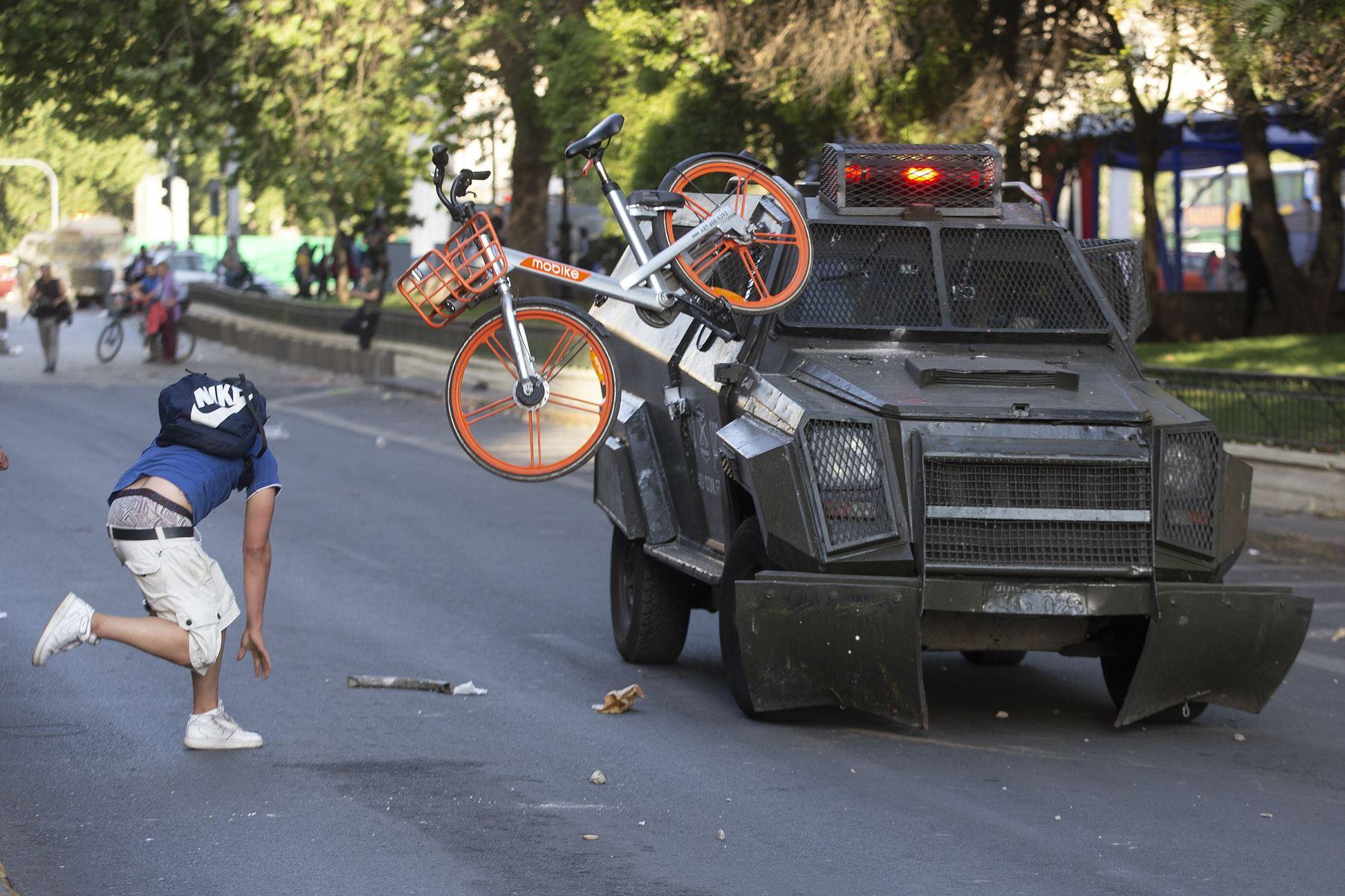 Los manifestantes se enfrentan con la policía antidisturbios después de una protesta masiva de evasión de tarifas en el centro de Santiago. AFP