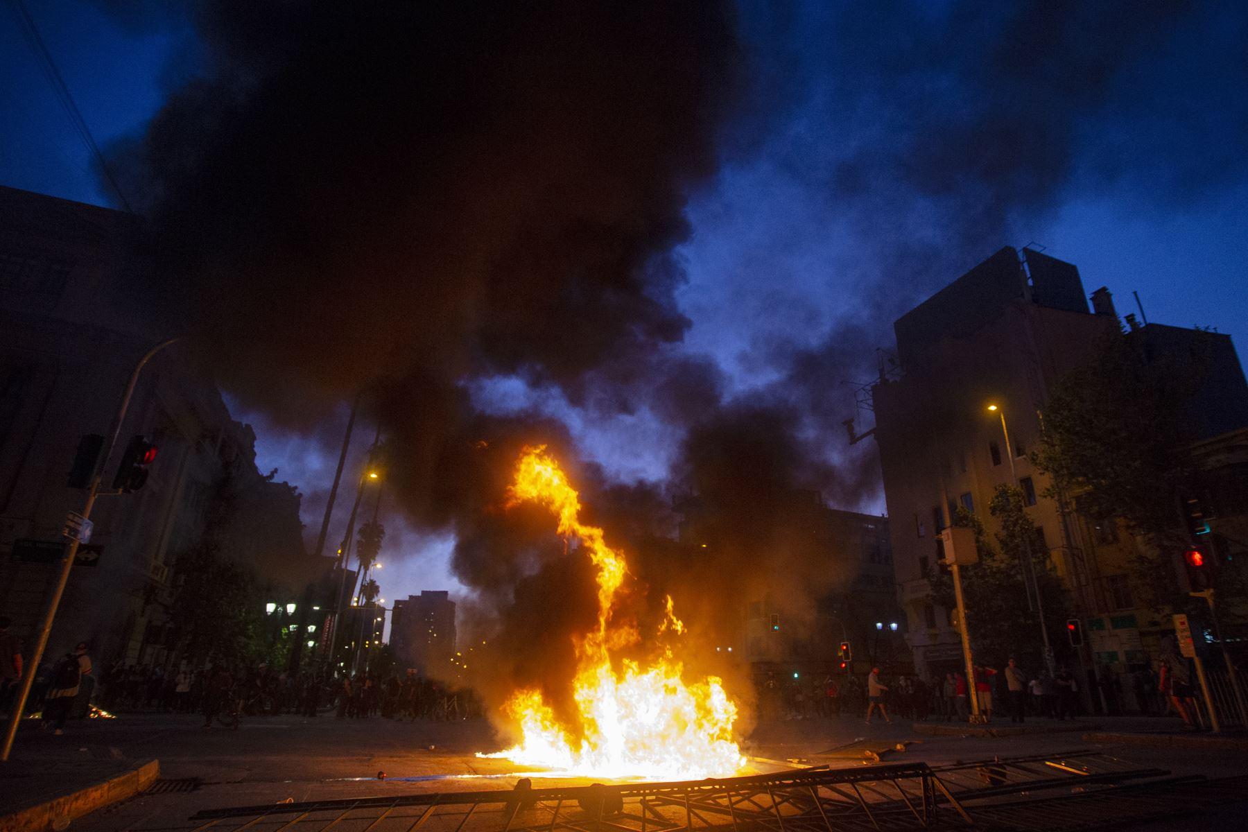 Una barricada arde en el centro de Santiago,  luego de una protesta masiva de evasión de tarifas. AFP