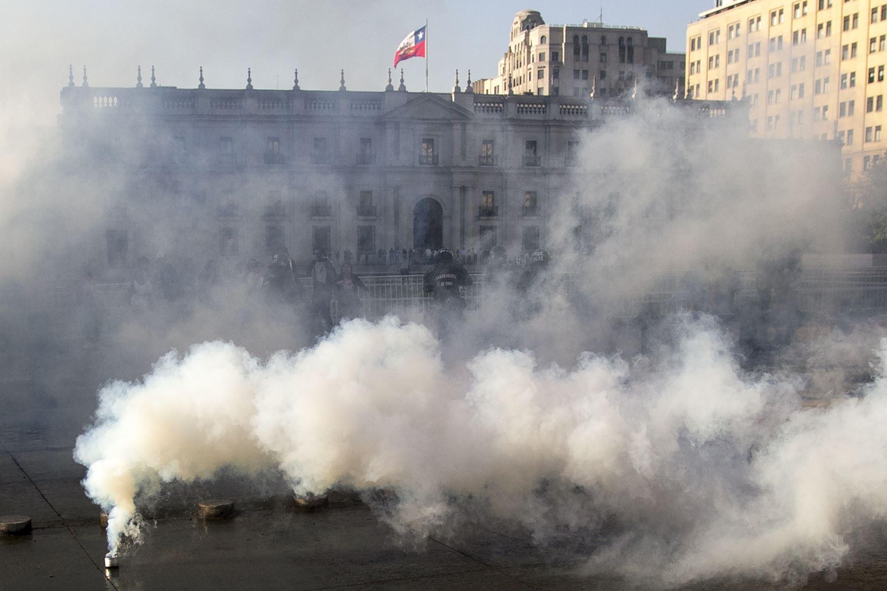 Los manifestantes se enfrentan con la policía antidisturbios después de una protesta masiva de evasión de tarifas frente al palacio de La Moneda, Santiago. AFP