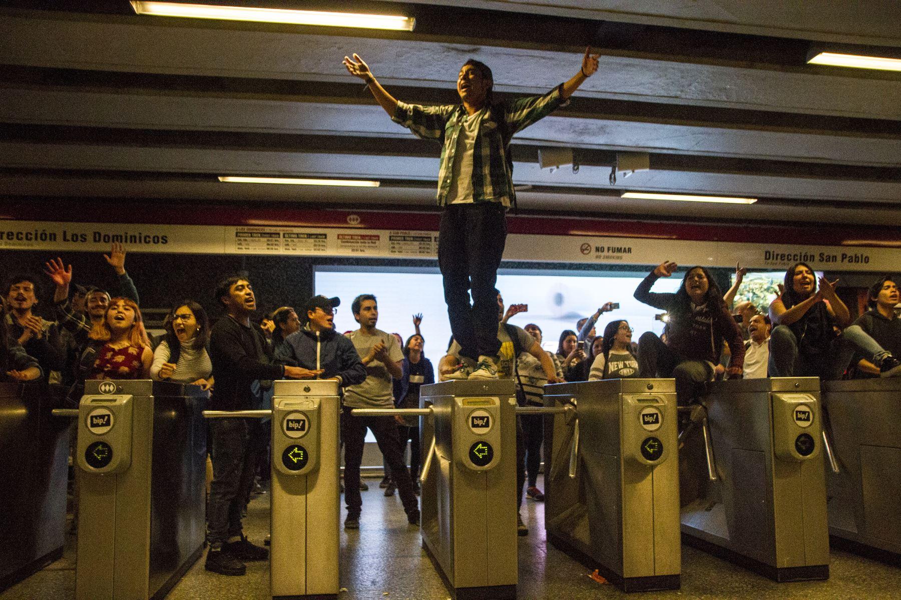 En esta foto publicada por Aton Chile, los estudiantes se manifiestan en la estación de metro Los Heroes durante una protesta masiva de evasión de tarifas en Santiago, Chile. AFP