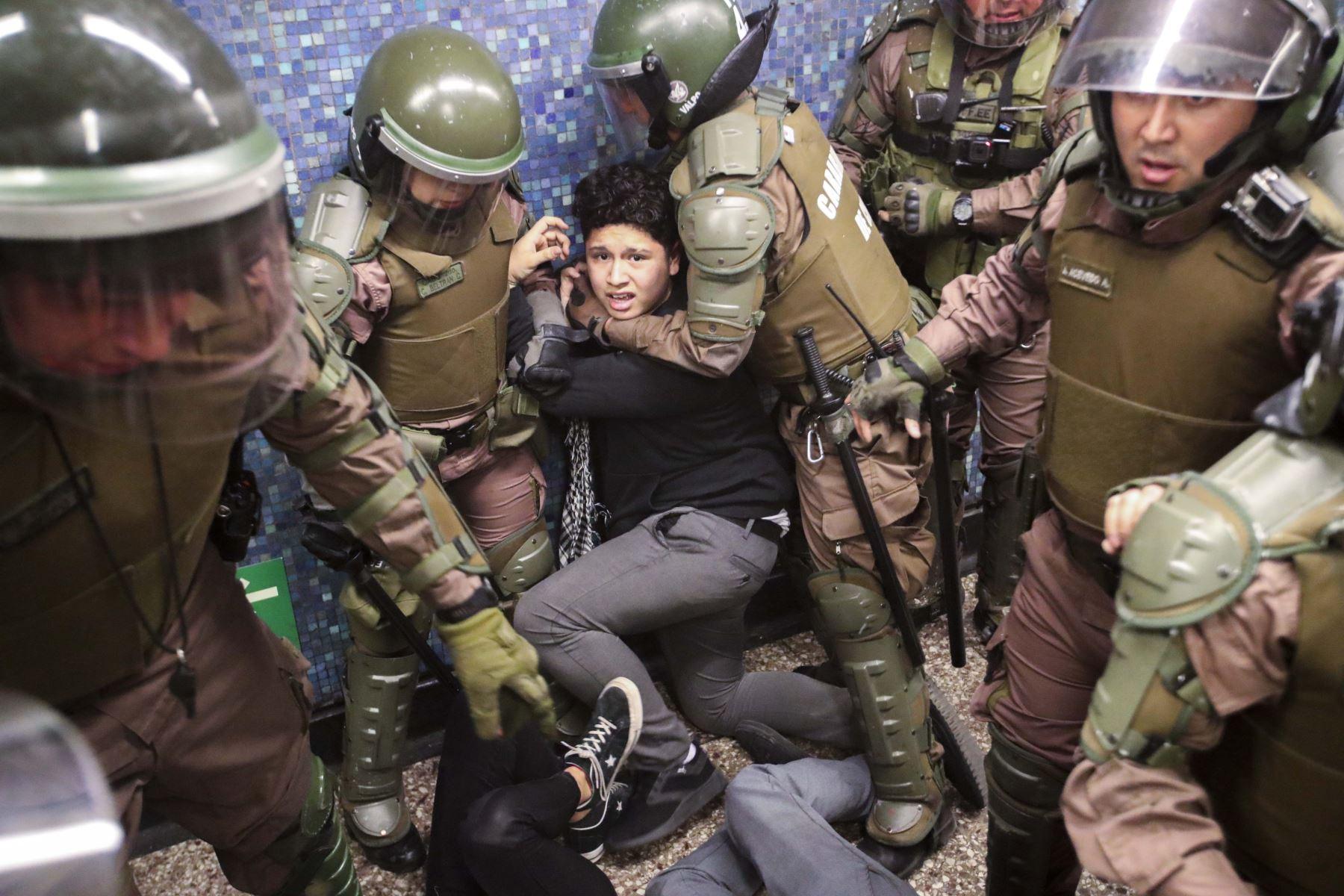 Carabineros detienen a estudiante durante una protesta masiva de evasión de tarifas en el metro de Santiago. Foto: EFE