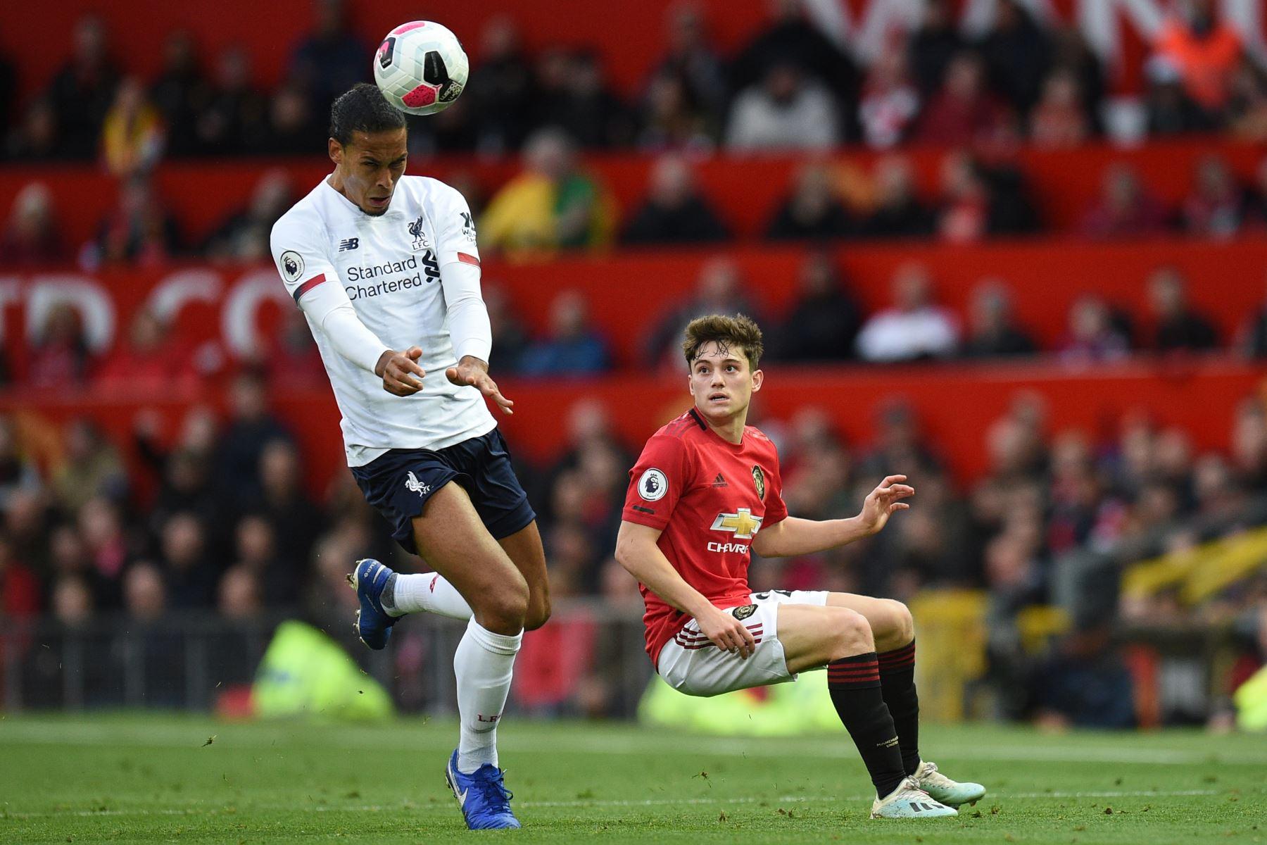 El defensor holandés del Liverpool Virgil van Dijk controla el balón con la cabeza ante marca del  centrocampista galés del Manchester United Daniel James en partido de Premier League. Foto: AFP