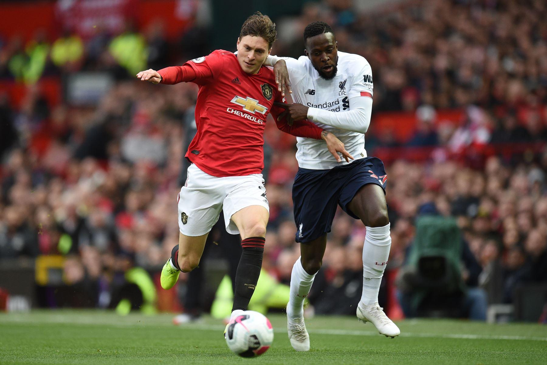 El defensor sueco del Manchester United, Victor Lindelof, compite con el delantero belga del Liverpool, Divock Origi, en partido por Premier League. Foto: AFP
