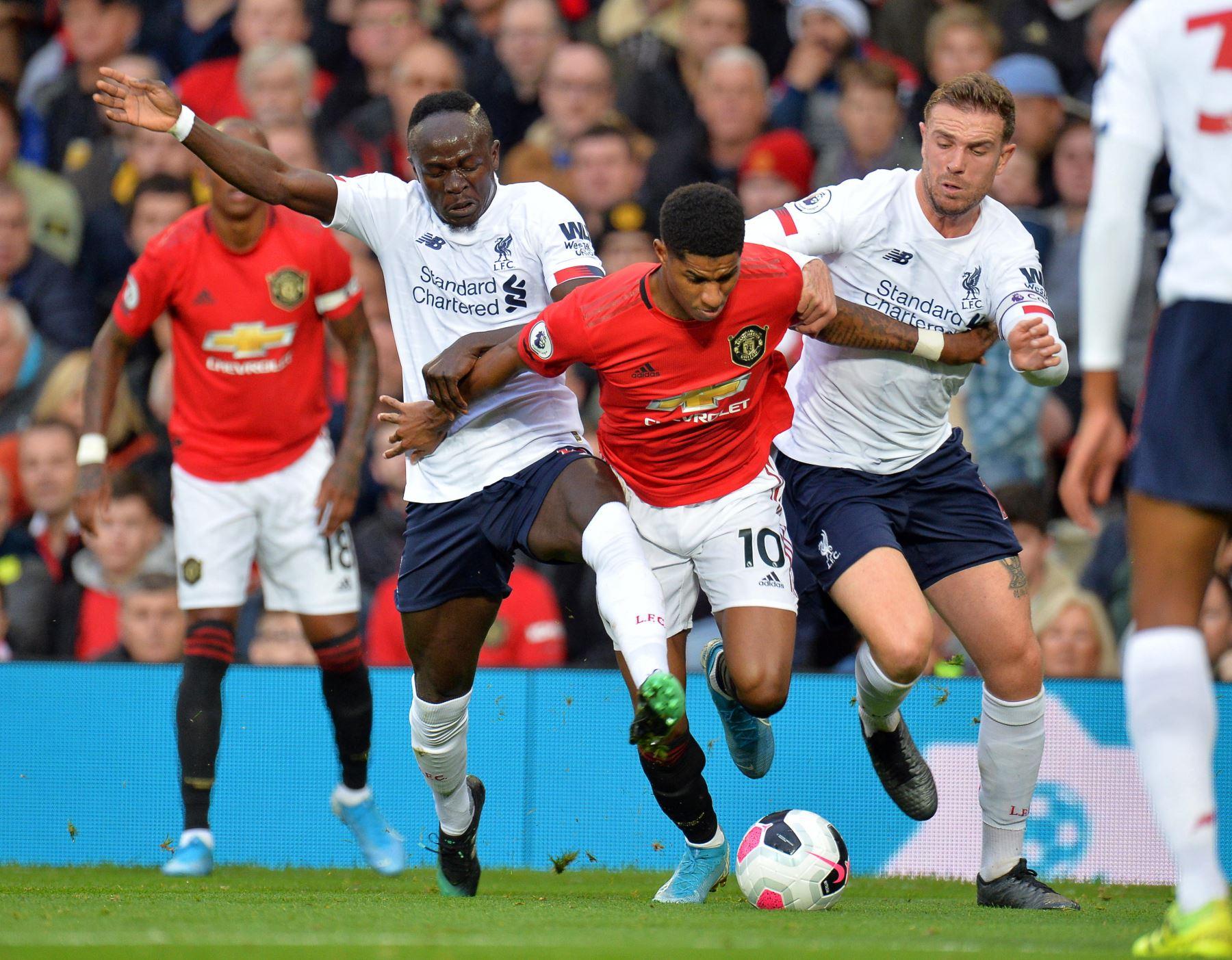 Marcus Rashford del Machester United evita fuerte marca del Liverpool. Foto: EFE