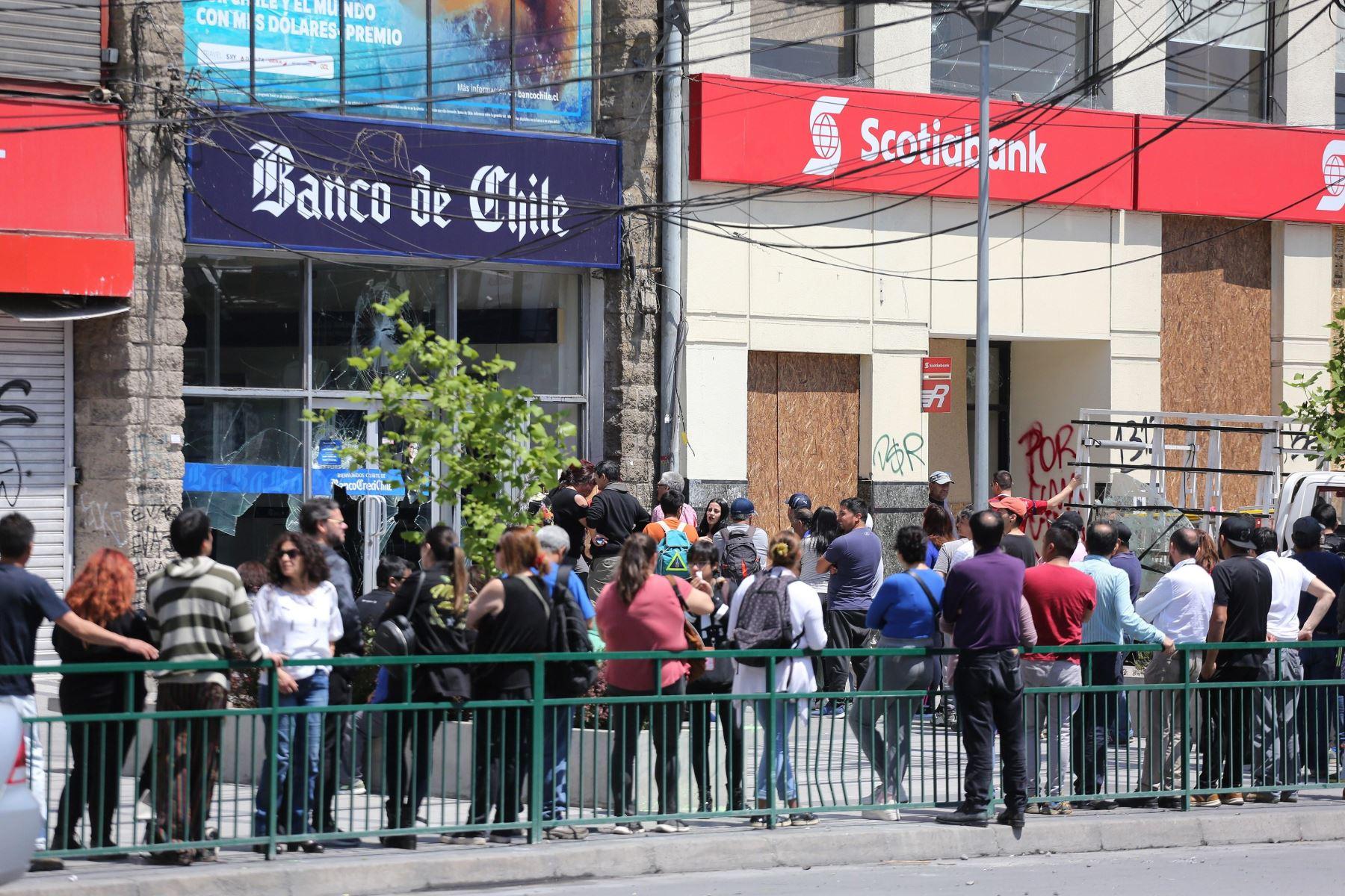 Ciudadanos hacen largas fila en os cajeros automáticos que lucen destruídos por enfrentamientos, en Santiago. Foto: EFE