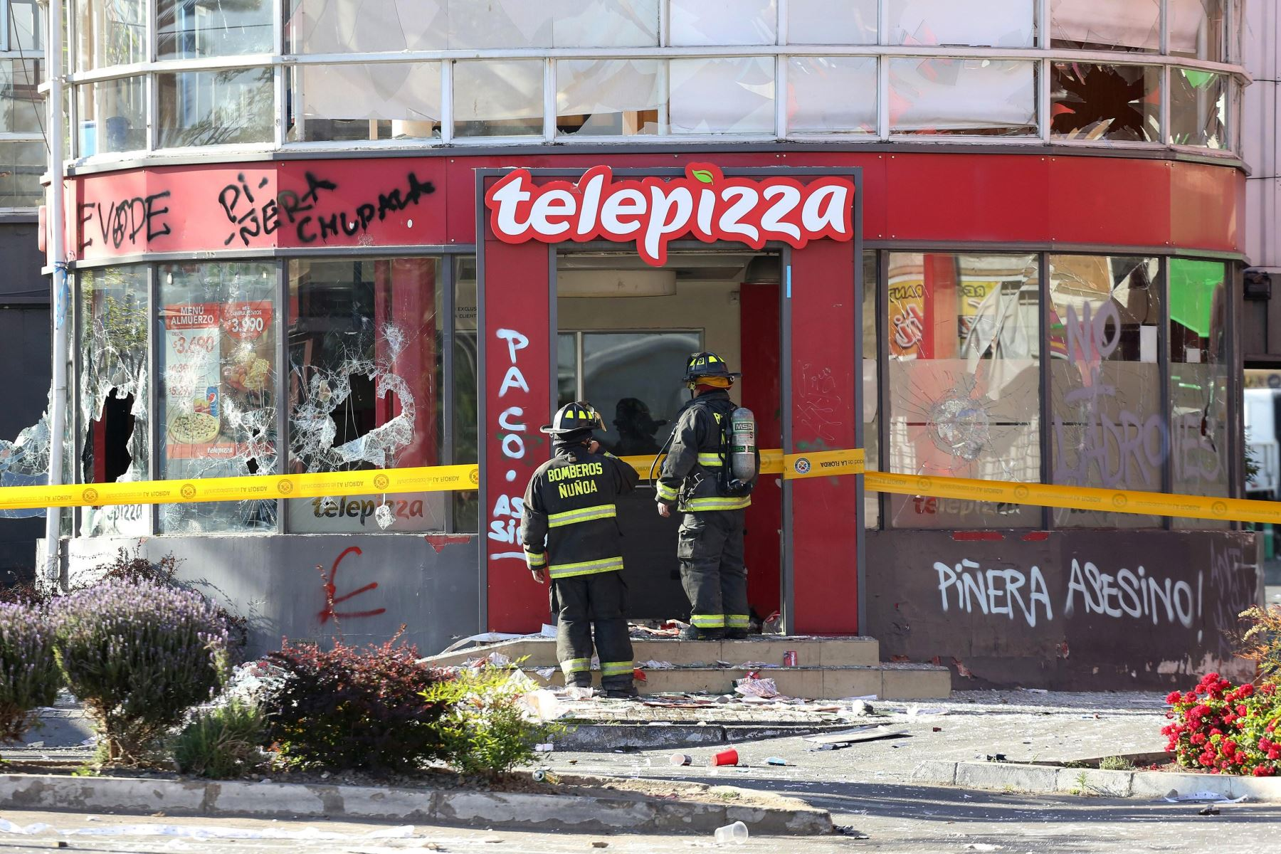Personal policial y bomberos inspeccionan un local de pizzas después de ser saqueado e incendiado por manifestantes, en medio de la coyuntura de protestas en Santiago. Foto: EFE