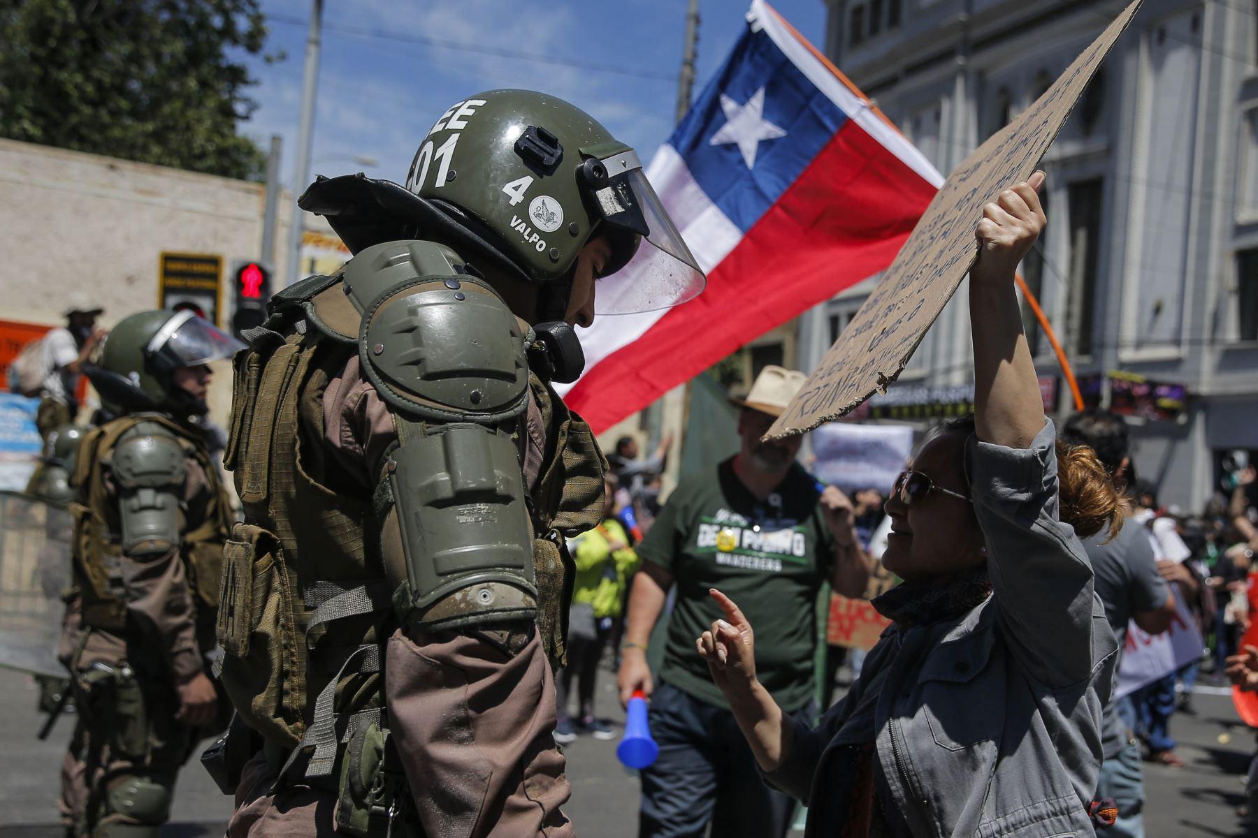 Una manifestante dialoga con un policía antidisturbios en Valparaíso en el quinto día consecutivo de protestas contra una subida ahora suspendida en los precios de los boletos del metro. Foto: AFP