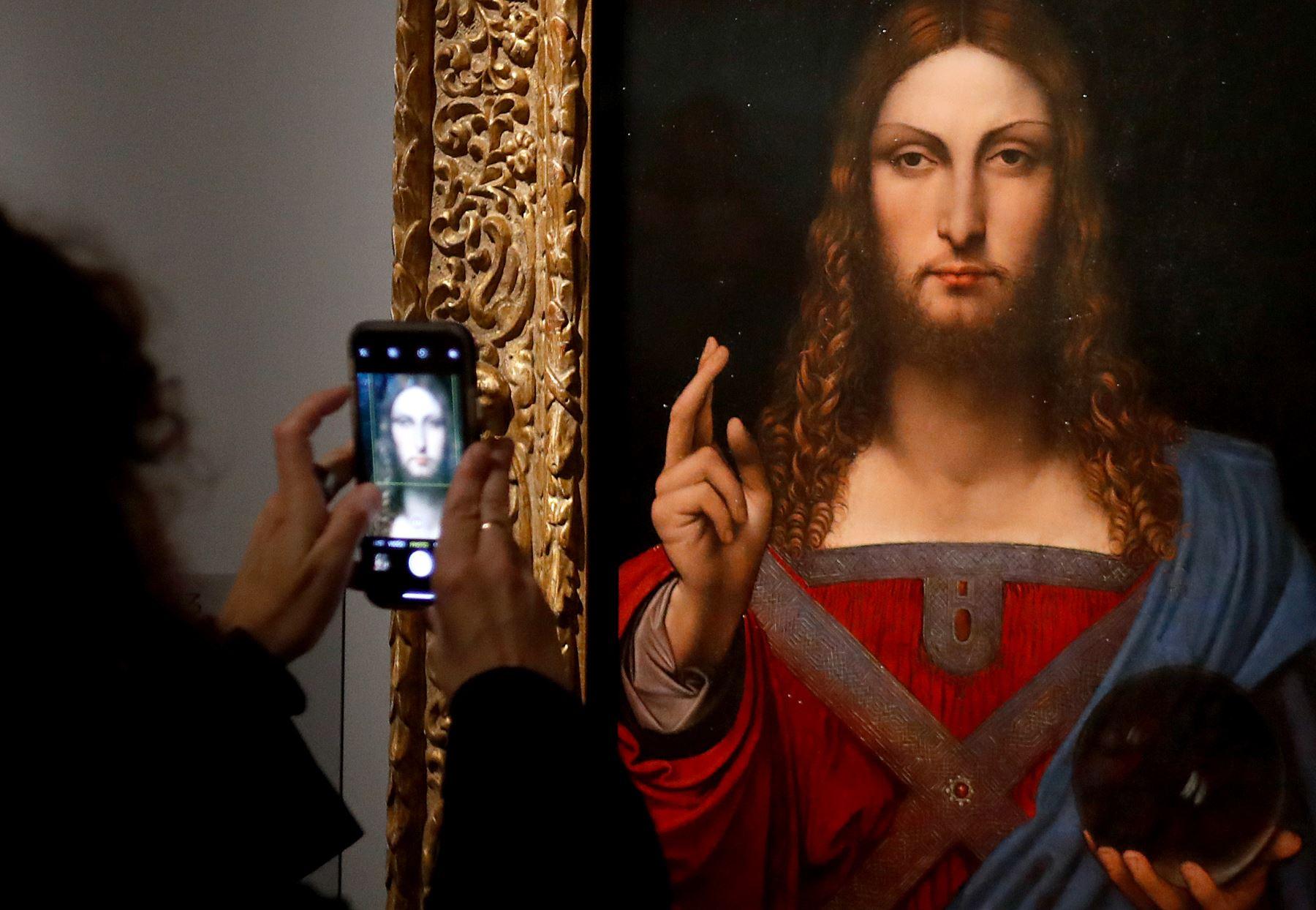 """Una persona toma una fotografía con un teléfono móvil en una pintura al óleo de """"Salvator Mundi"""" de Leonardo da Vinci, durante la inauguración de la exposición """"Leonardo da Vinci"""", el 22 de octubre de 2019 en el museo del Louvre. Foto: AFP"""