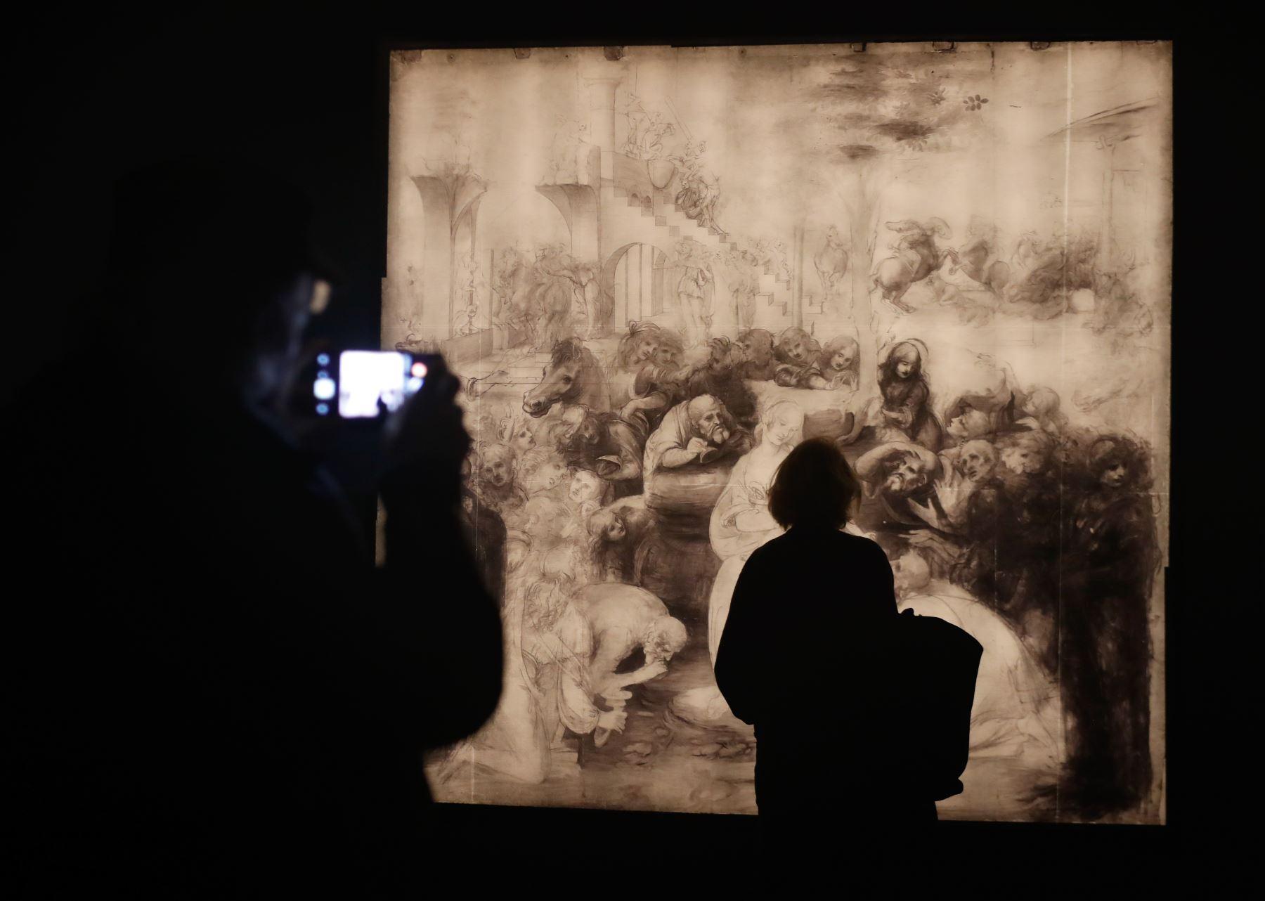 """Una persona mira una reflectografía infrarroja de """"La adoración de los magos"""" de Leonardo da Vinci durante la inauguración de la exposición """"Leonardo da Vinci"""", en el museo del Louvre en París. Foto: AFP"""